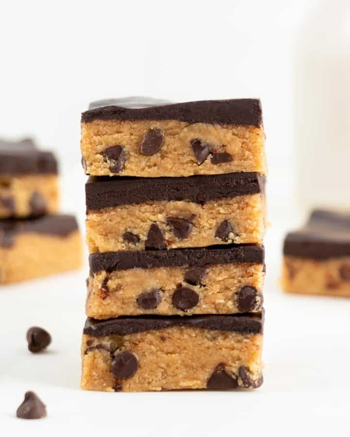 four no bake cookie dough bars stacked in front of a glass of almond milk