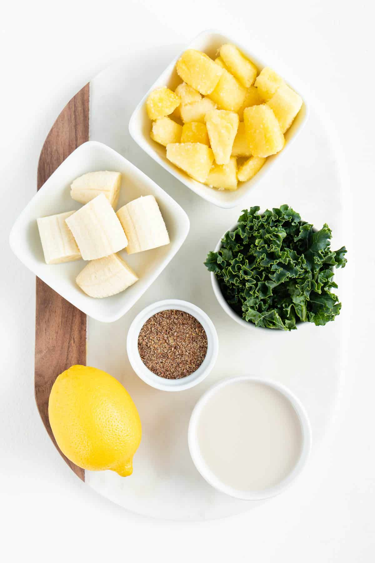 white bowls filled with sliced banana, pineapple, kale, flaxseed meal, lemon, and coconut milk on a white marble board