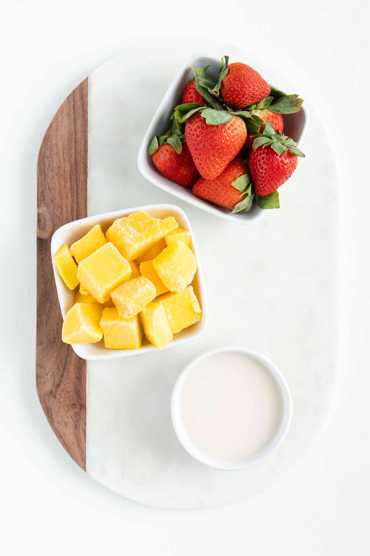 two bowls of fresh fruit and a glass of almond milk on top of a white marble board