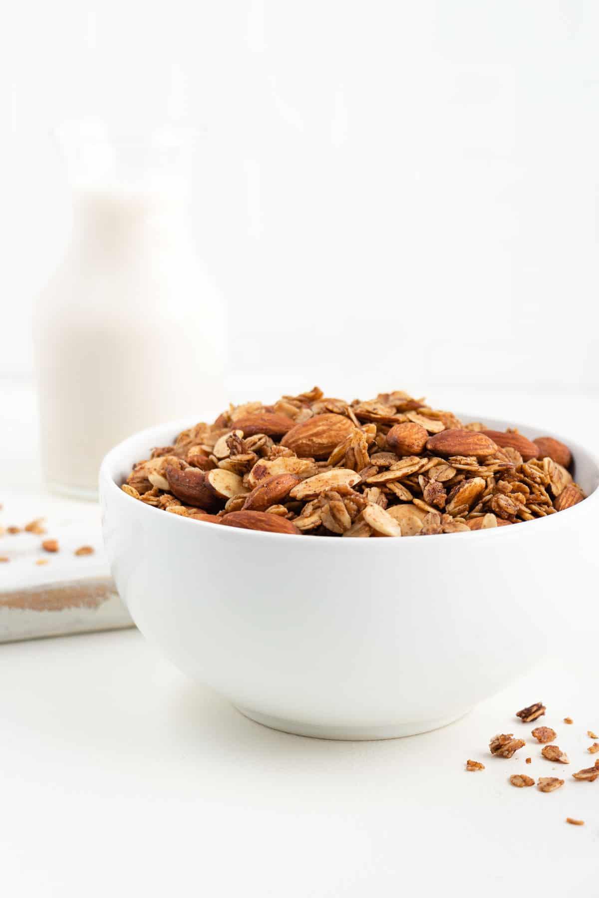 vanilla almond granola in a white bowl beside a glass of milk