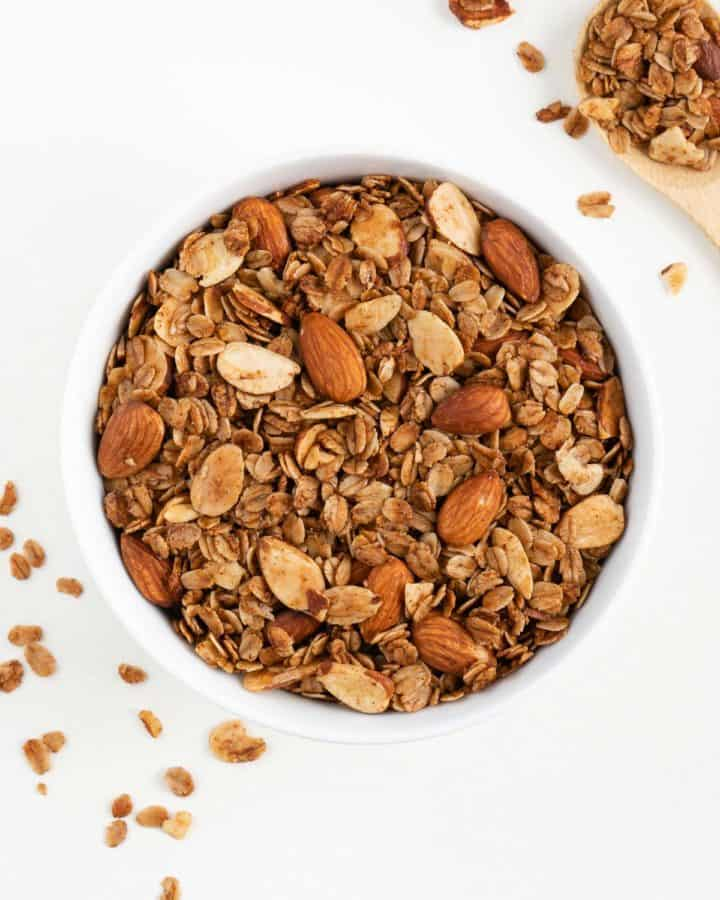 a white bowl filled with vanilla almond granola beside a wooden spoon