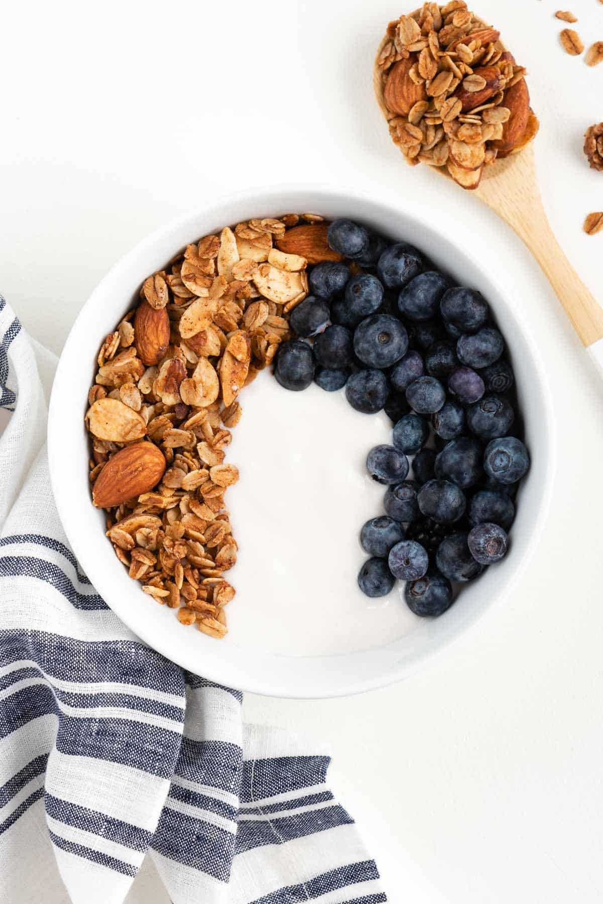 yogurt, granola, and blueberries inside a white bowl beside a blue and white striped napkin