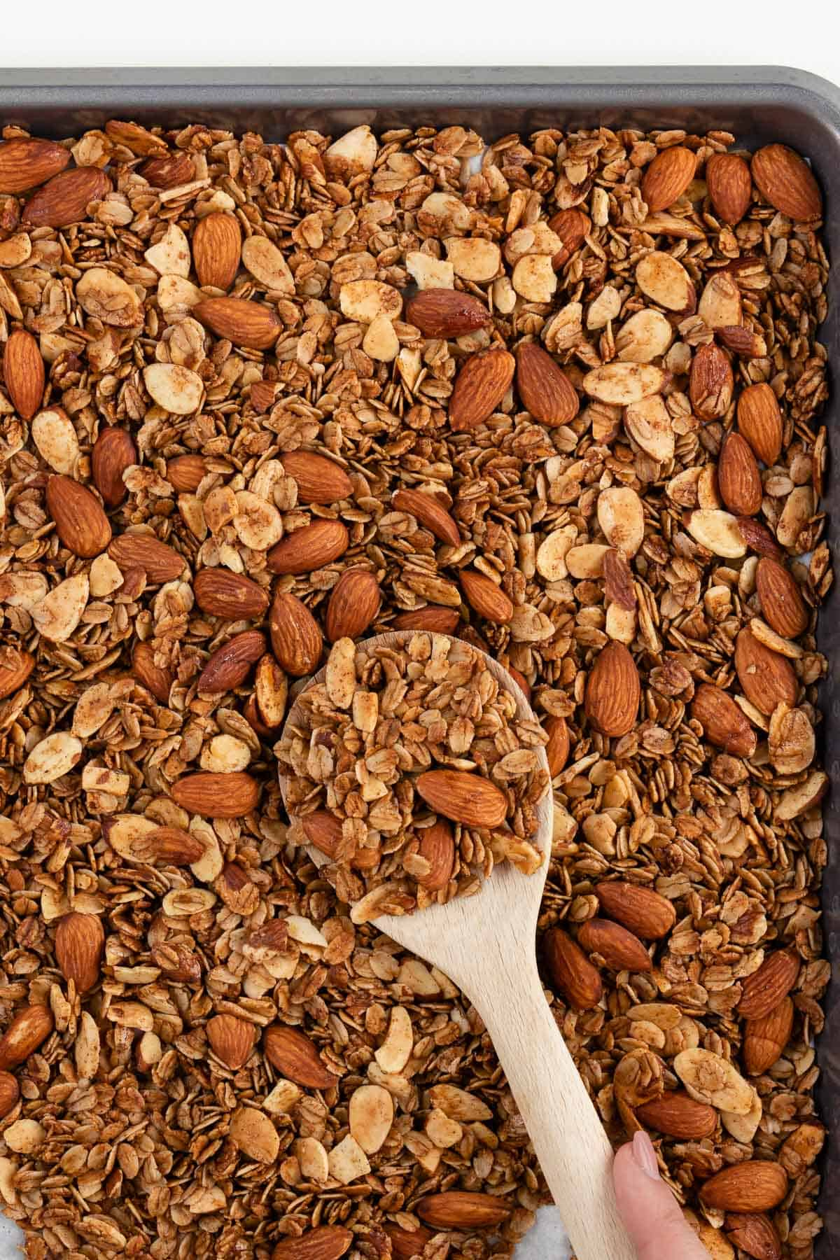 a wooden spoon scooping granola off of a baking pan