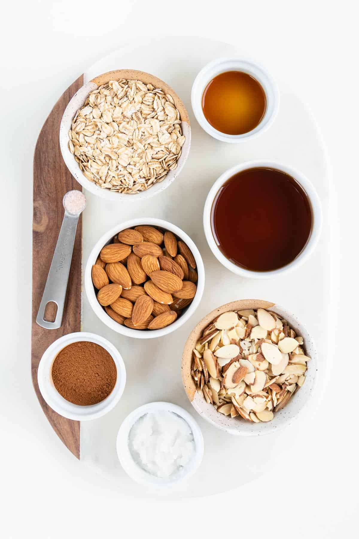 small bowls filled with oats, nuts, cinnamon, maple syrup, and coconut oil on a white marble board