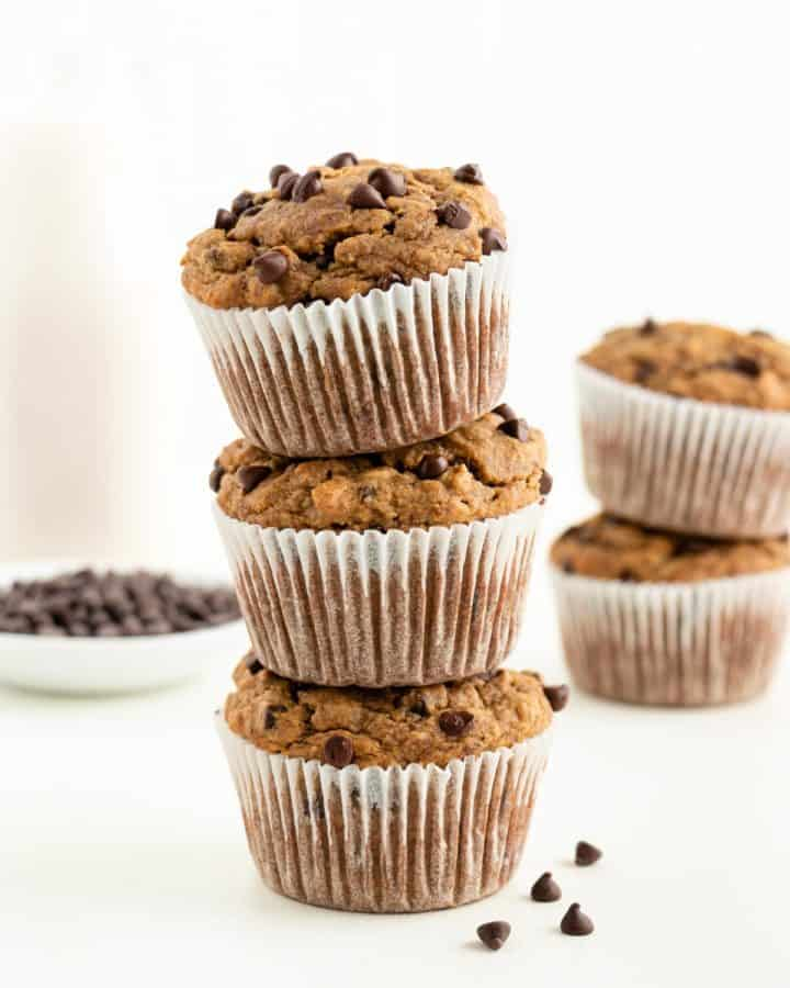 three gluten-free vegan banana chocolate chip muffins stacked on top of each other in front of a glass of almond milk and bowl of chocolate