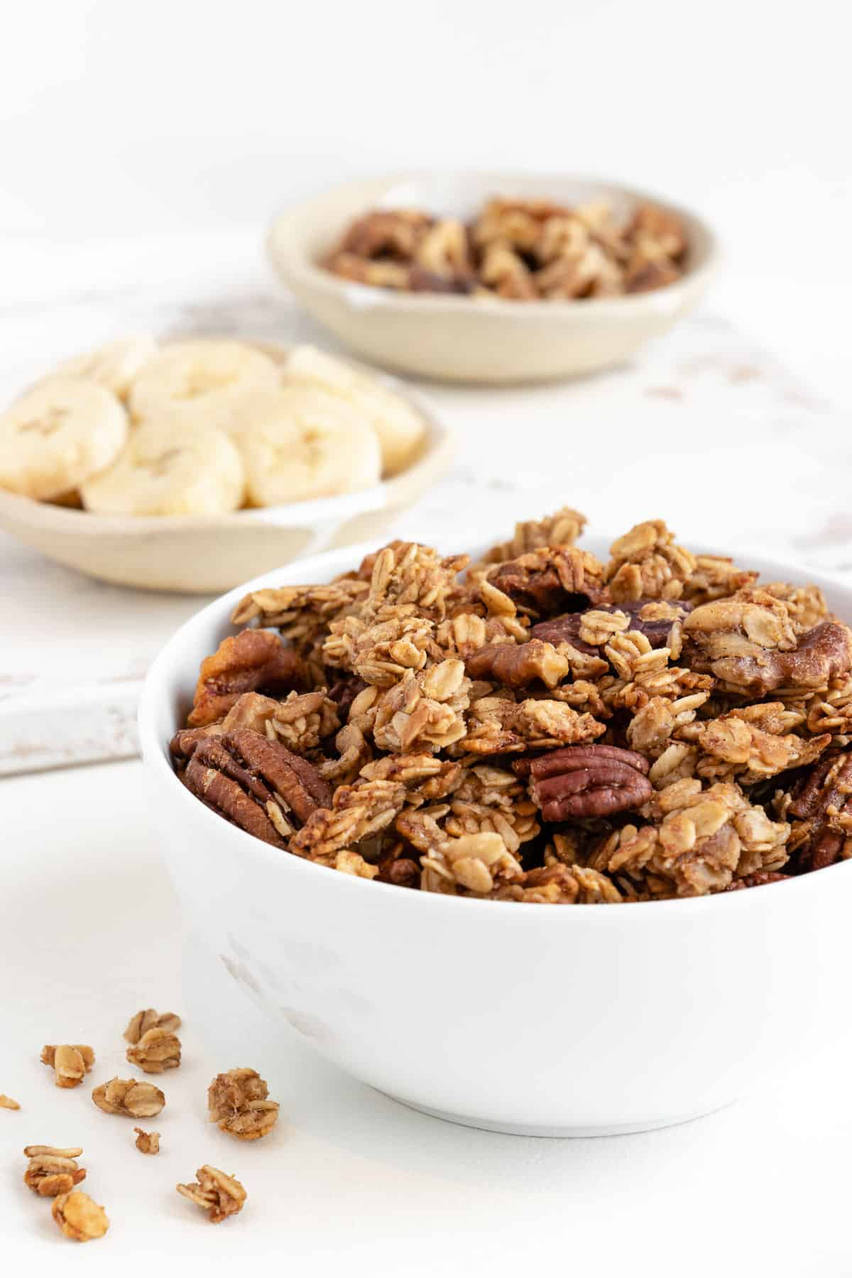 banana bread granola in a white bowl with sliced bananas and walnuts behind it