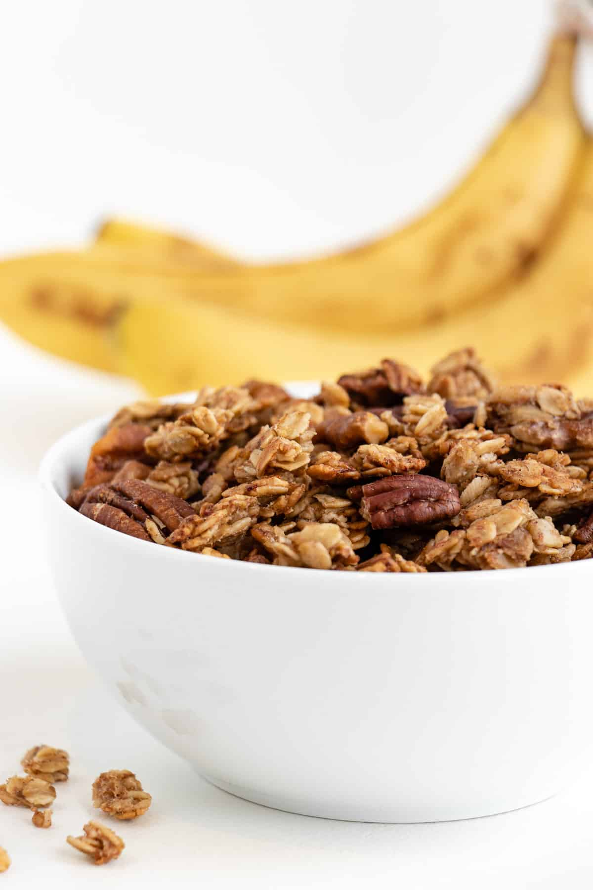 granola inside a white bowl in front of three bananas