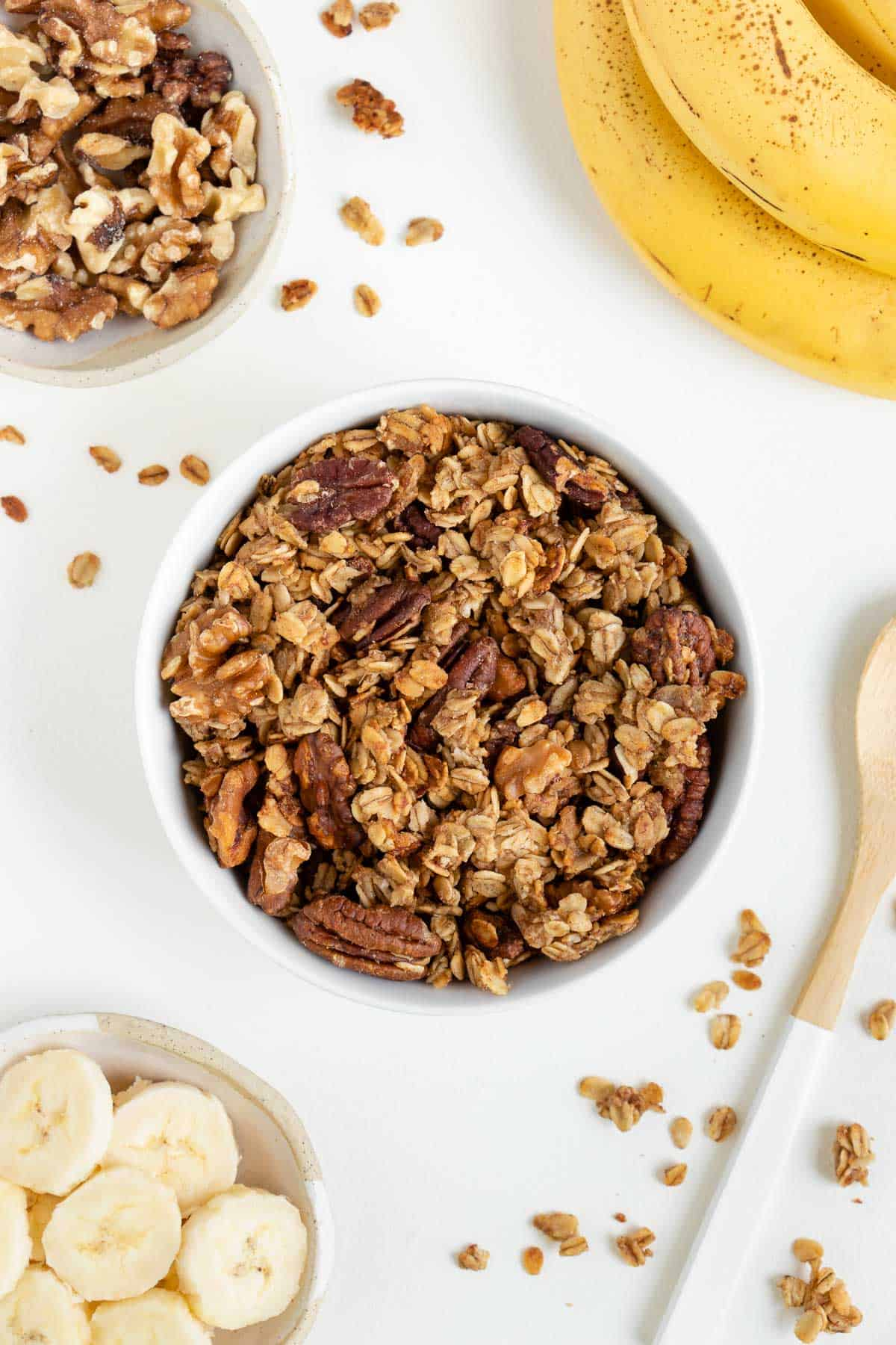 banana bread granola inside a white bowl surrounded by walnuts, sliced banana, and banana peels