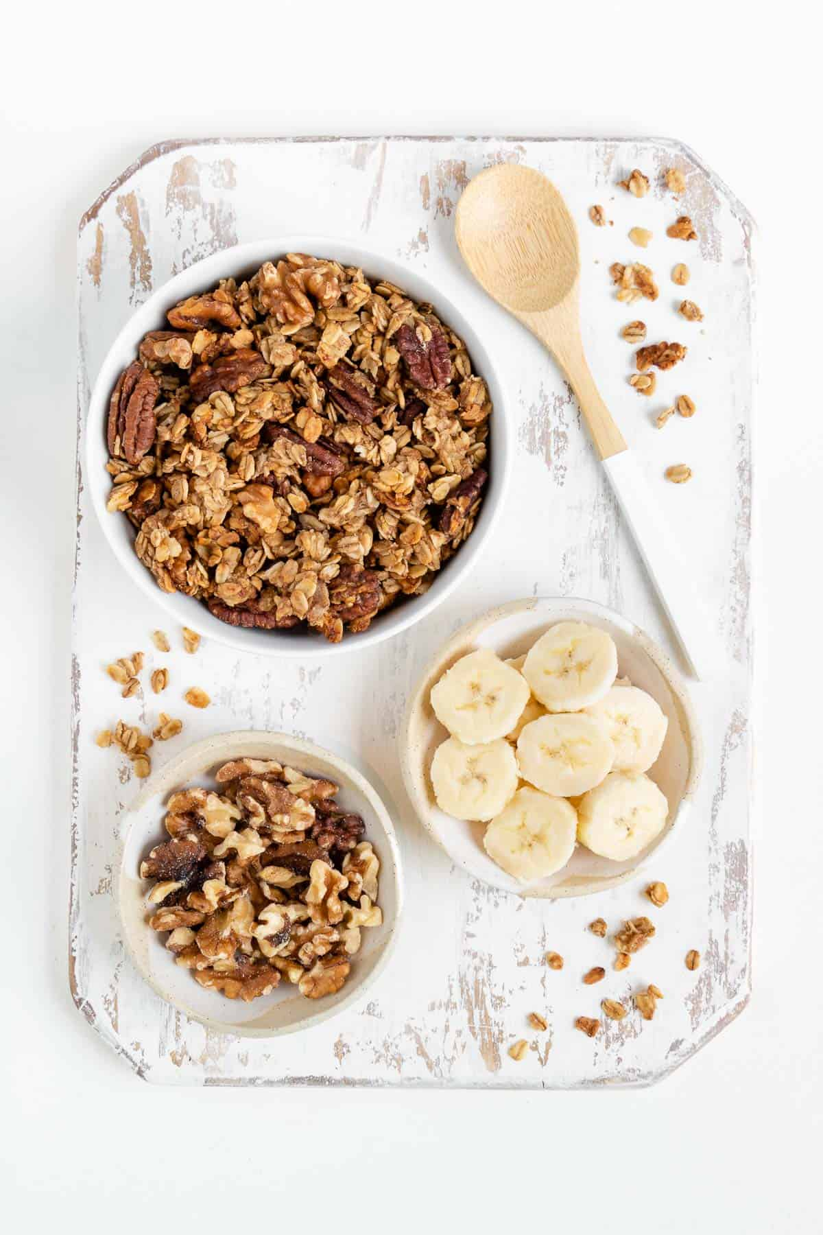 a bowl of banana bread granola, a bowl of sliced bananas, and a bowl of walnuts on a distressed wood cutting board