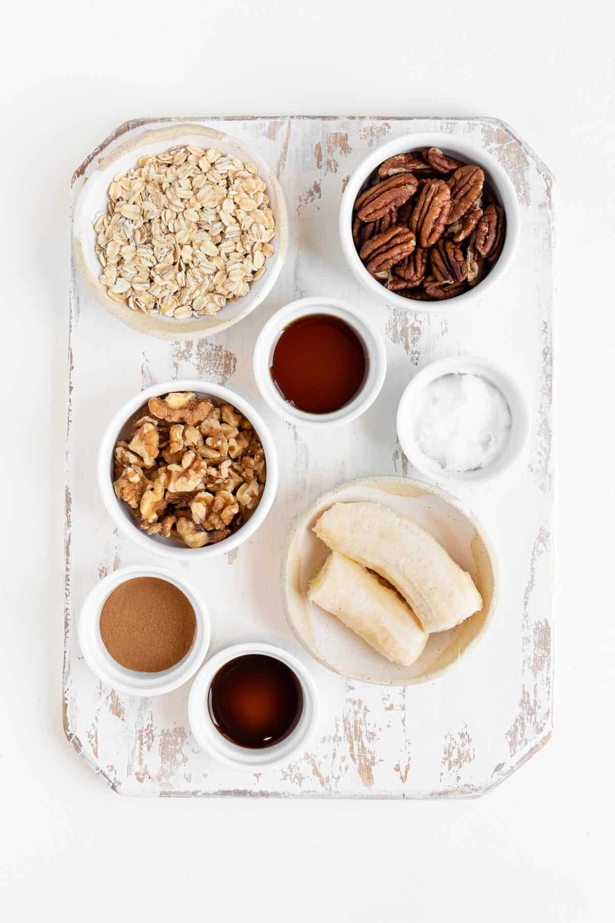 oats, cinnamon, walnuts, pecans, maple syrup, and coconut oil in white bowls on a distressed cutting board