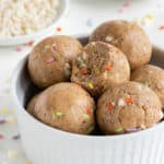 birthday cake energy balls stacked inside a white bowl beside white chocolate chips and sprinkles