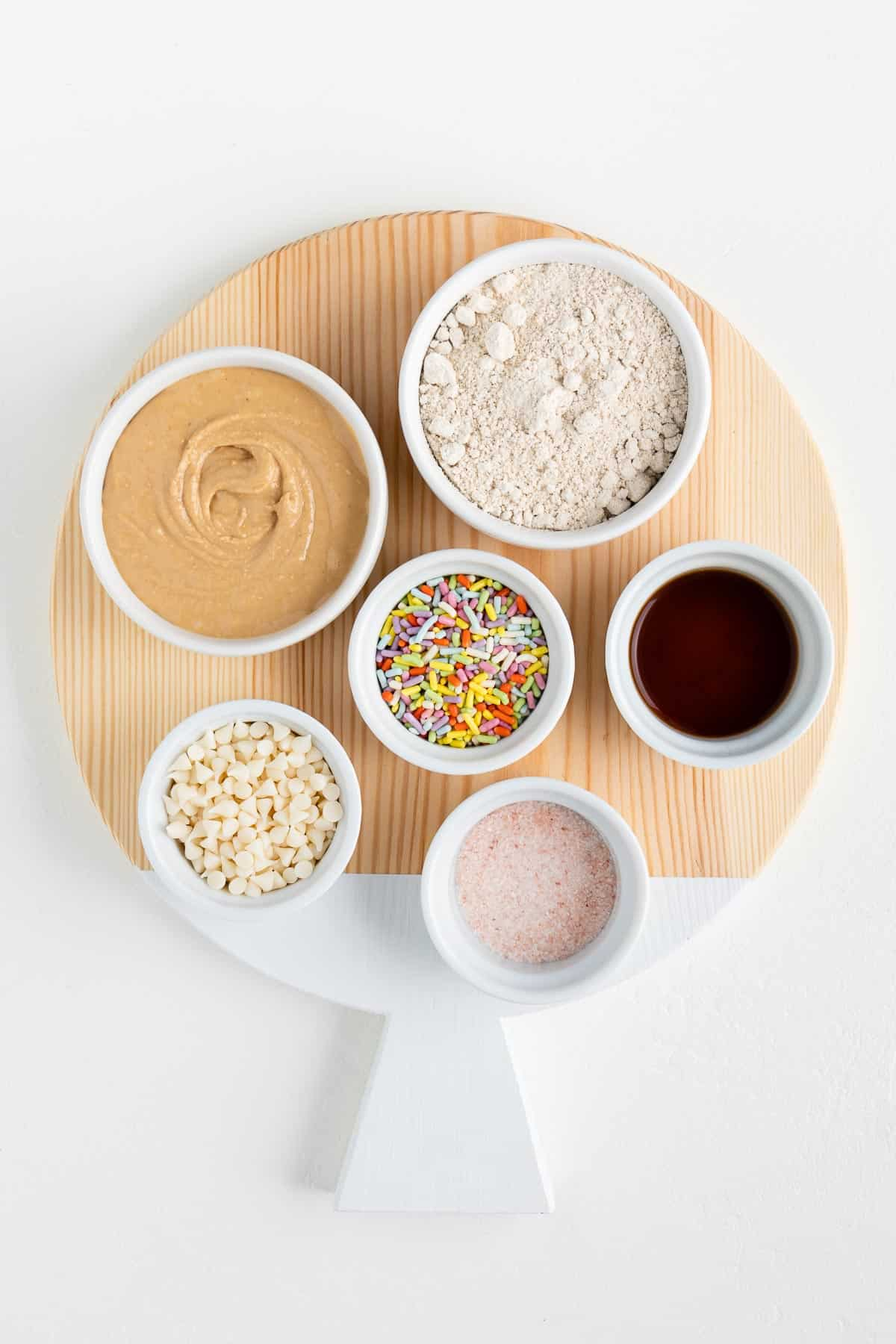 round wooden cutting board with cashew butter, sprinkles, oat flour, vanilla extract, and white chocolate chips in small white bowls