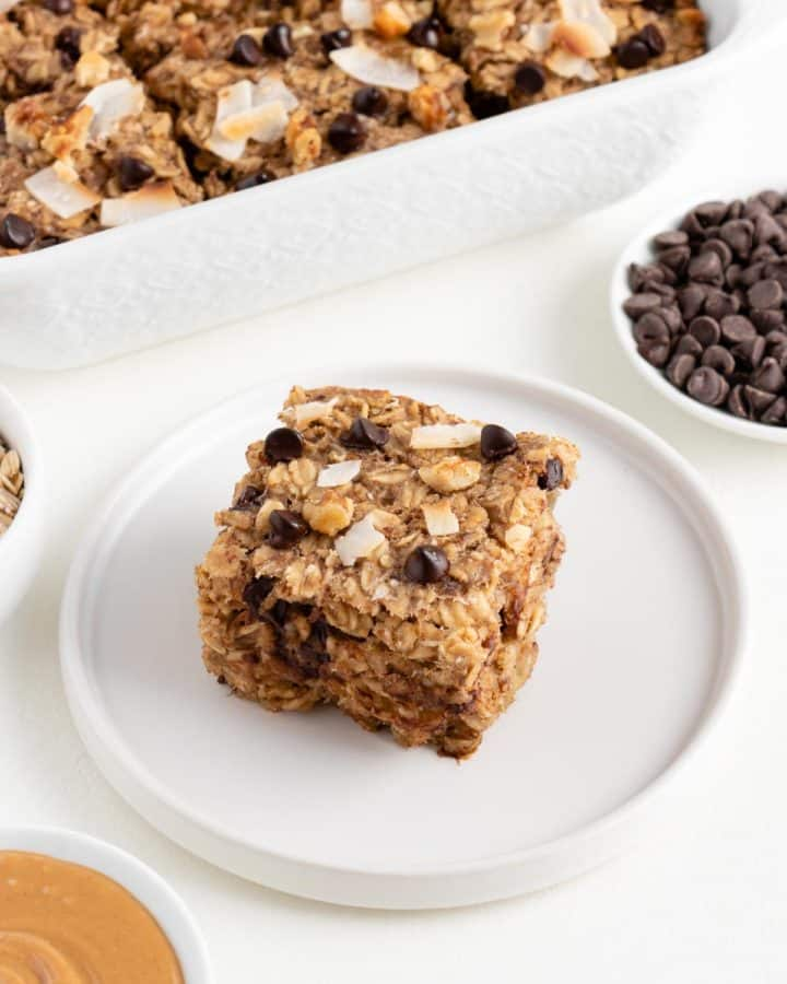 a square of chunky monkey baked oatmeal on a white plate surrounded by a small bowl of chocolate chips