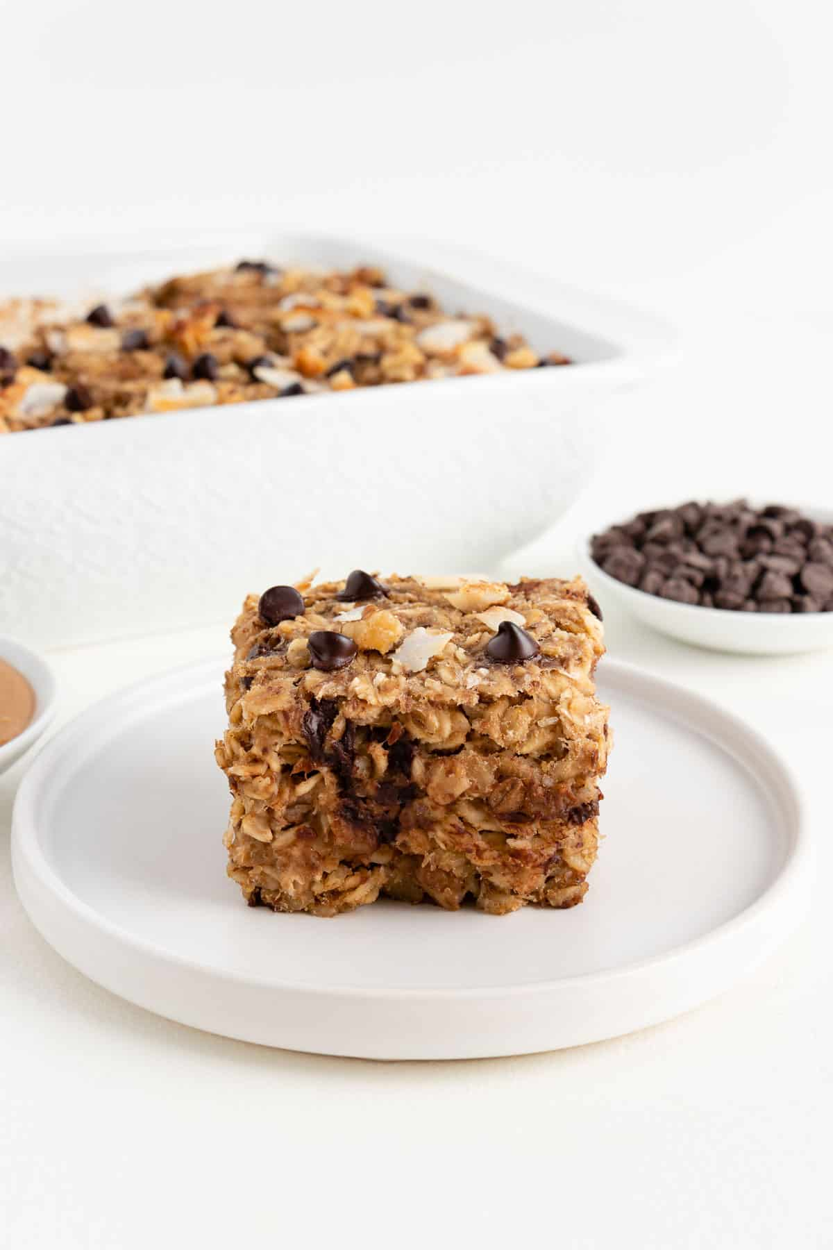 a square of chunky monkey baked oatmeal on a white plate beside a bowl of chocolate chips