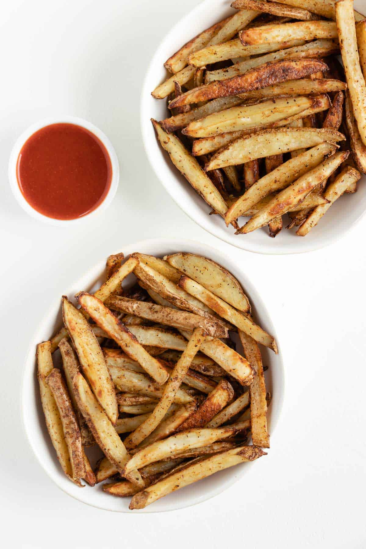 two white bowls filled with crispy baked french fries beside a bowl of ketchup