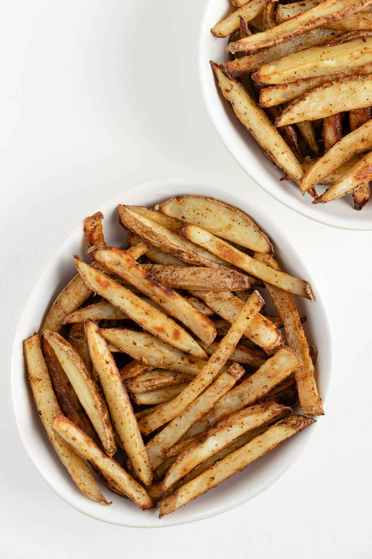 two white bowls filled with crispy baked french fries