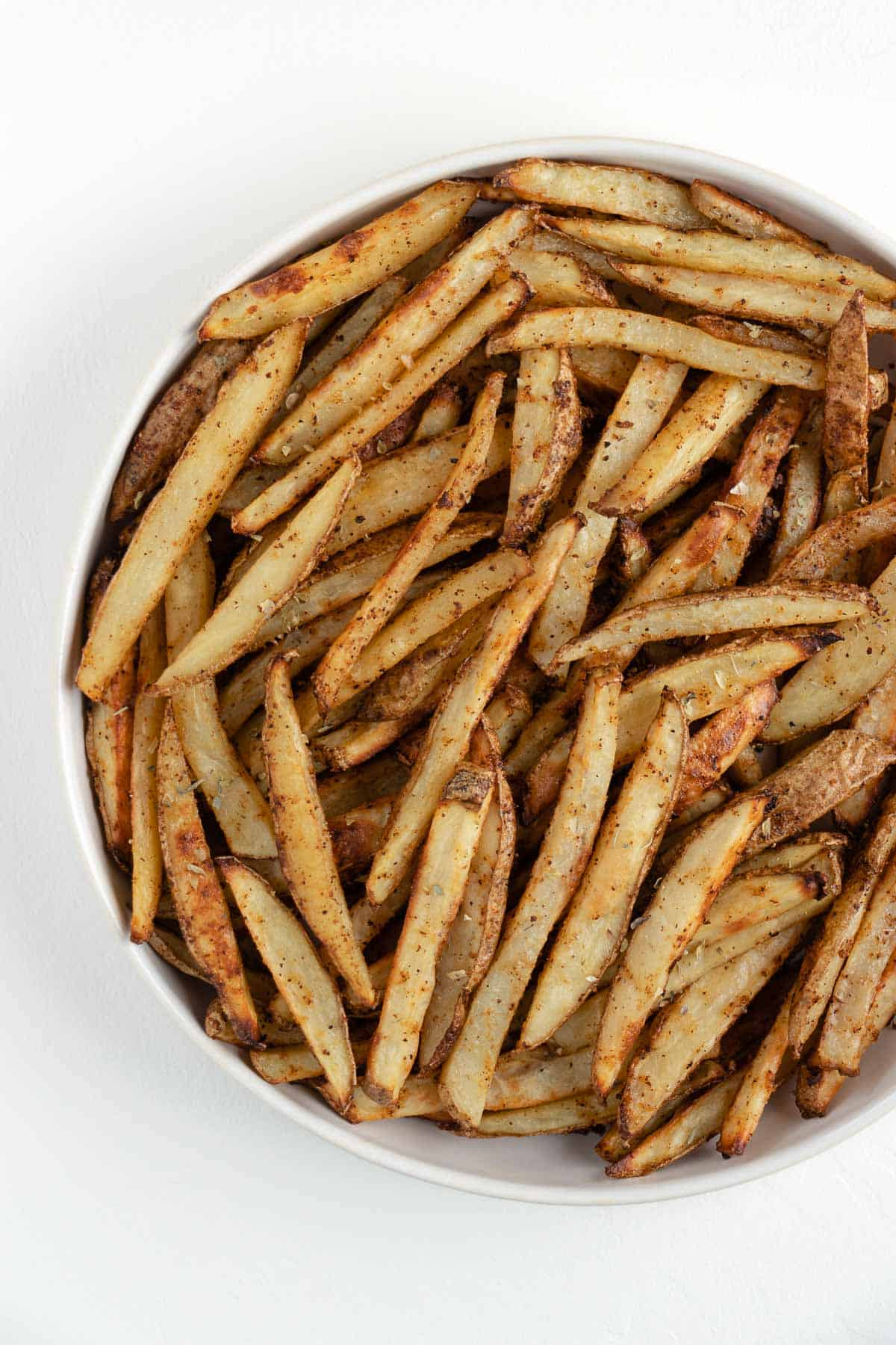 crispy baked french fries in a white bowl