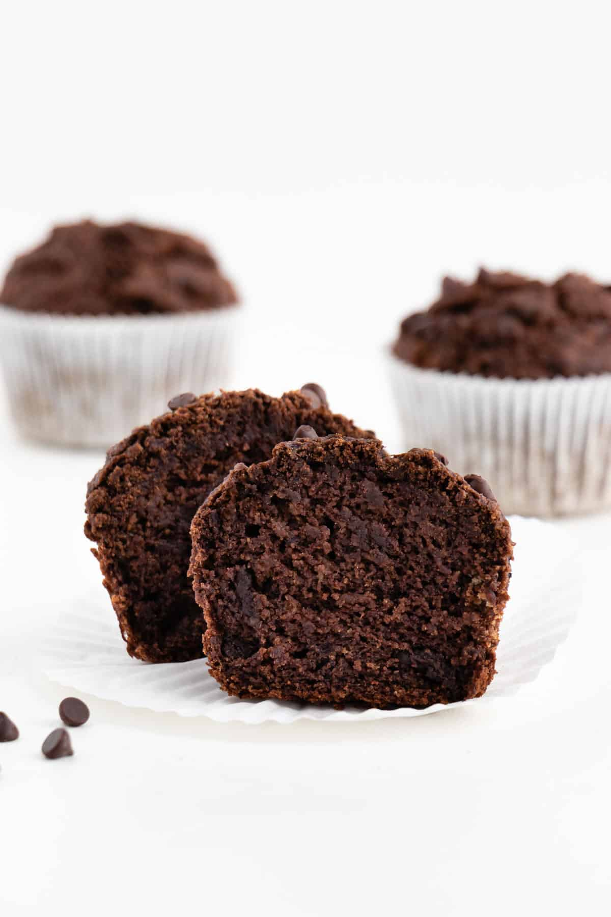 a sliced double chocolate banana muffin in front of two whole muffins