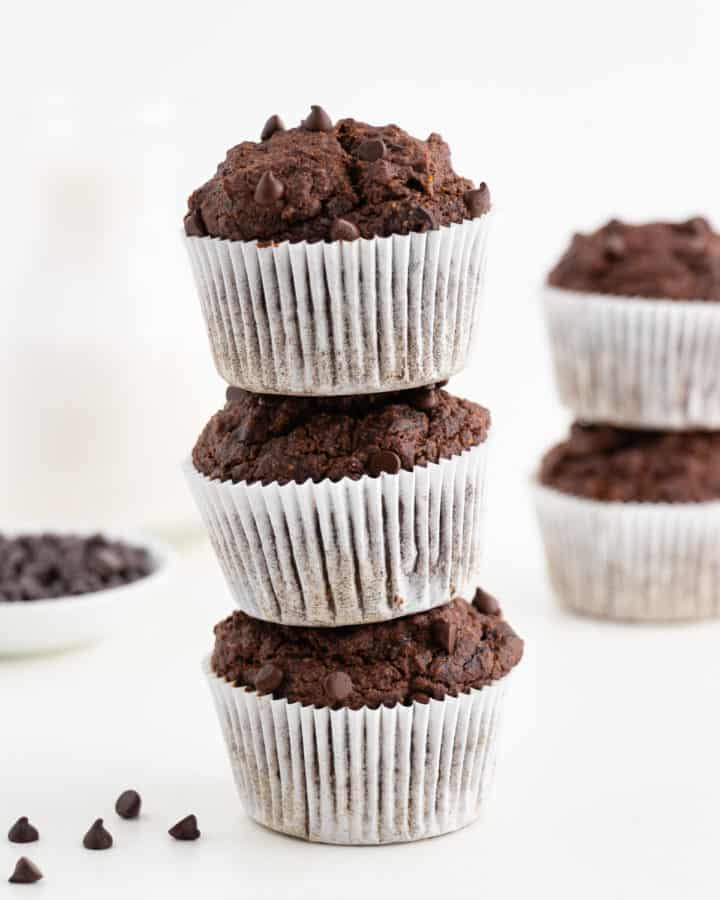 a stack of three vegan gluten-free double chocolate banana muffins in front of a glass of almond milk and bowl of chocolate chips