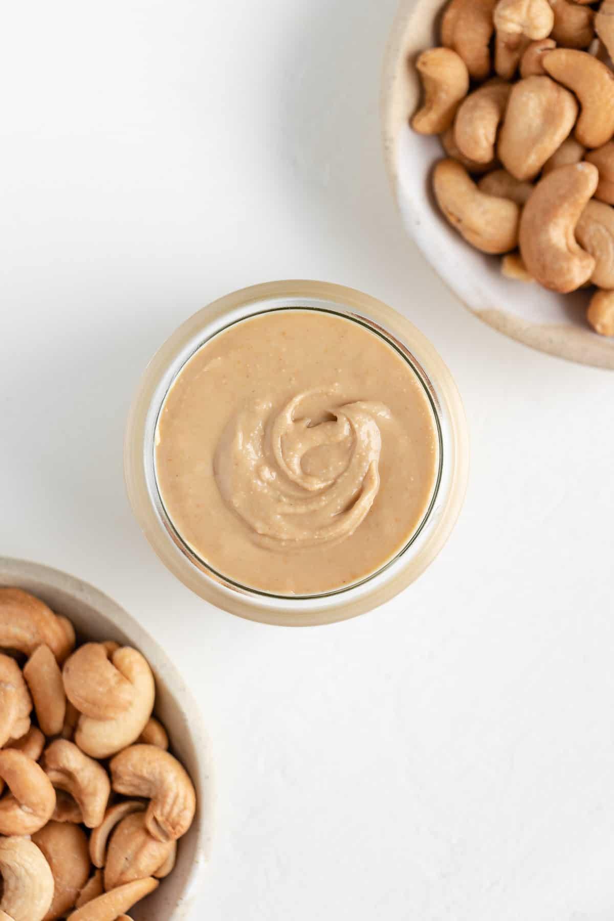homemade cashew butter inside a glass jar beside two bowls of roasted cashews