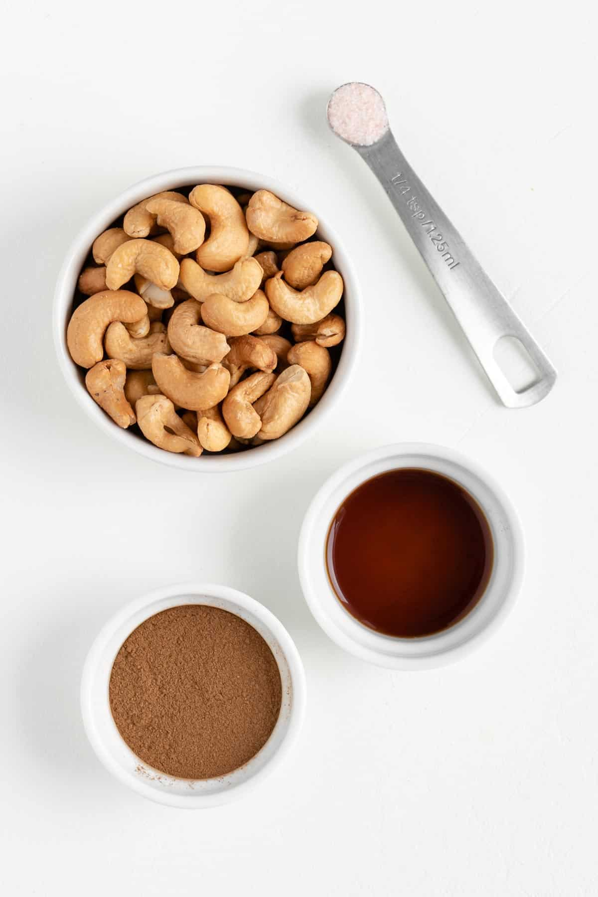a bowl of cashews beside a bowl of vanilla extract, coconut sugar, and salt