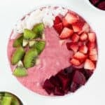 strawberry beet smoothie bowl topped with coconut flakes, kiwi fruit, strawberries, and beets