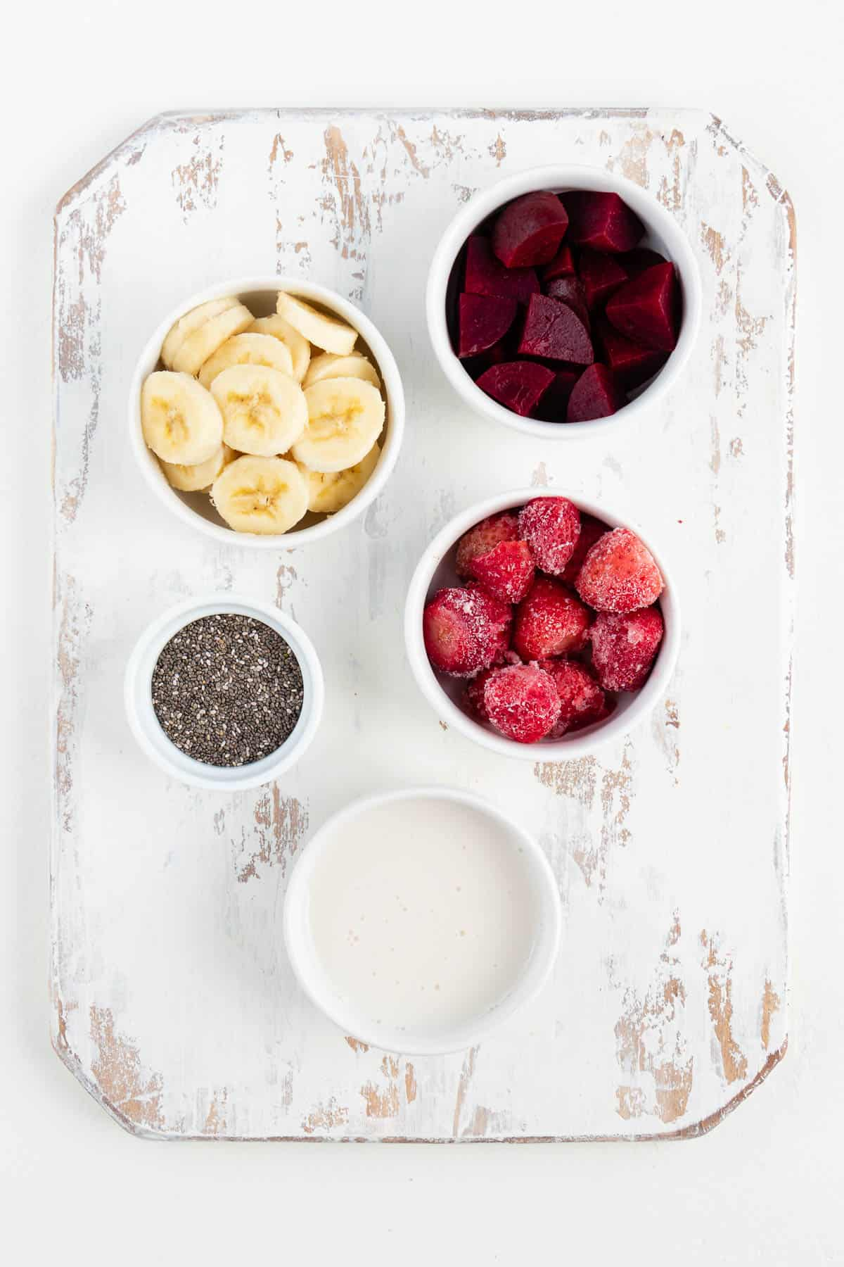 small white bowls filled with bananas, berries, chia seeds, and coconut milk