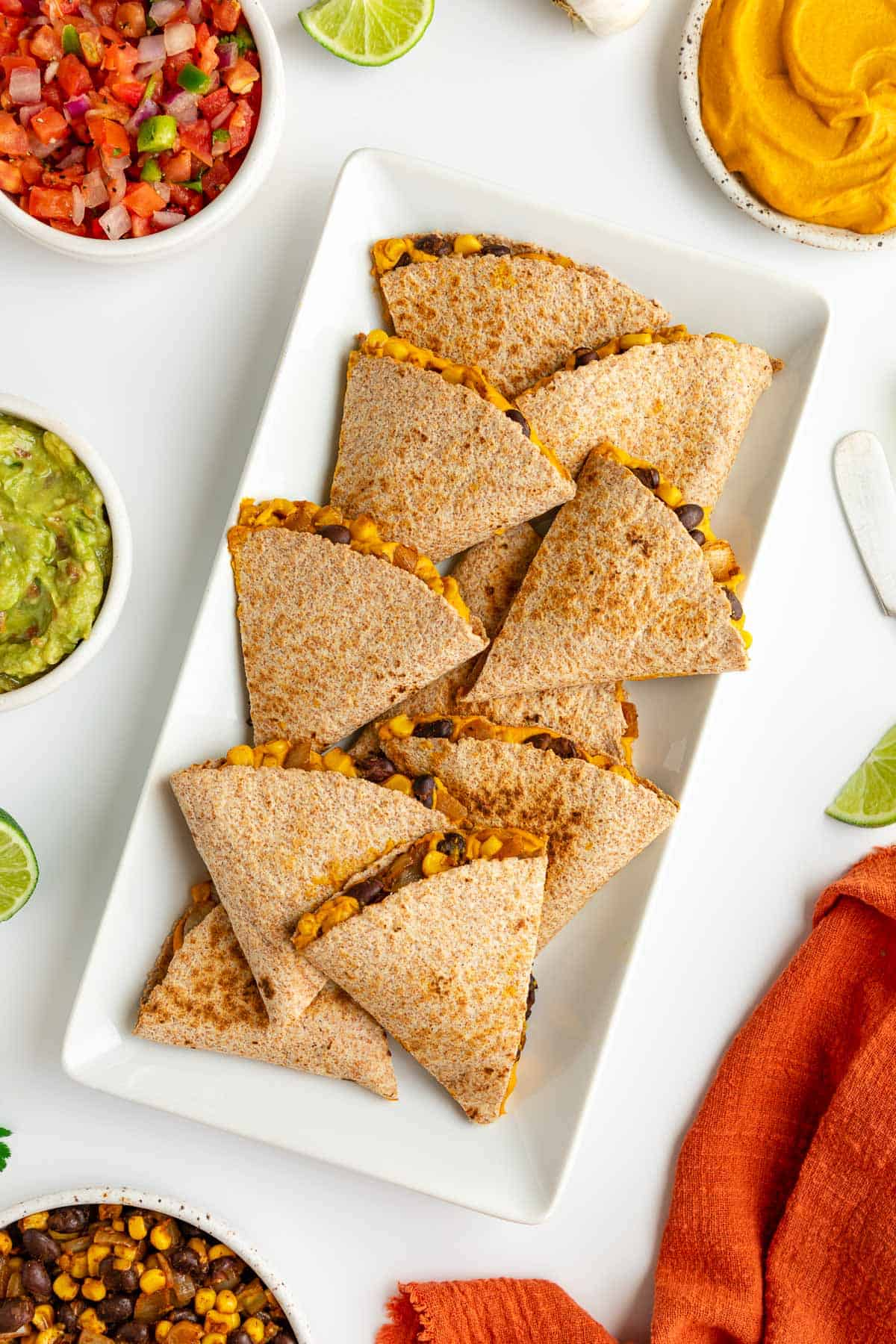 sweet potato black bean quesadillas on a white plate surrounded by bowls of guacamole, salsa, pico de gallo, and cilantro