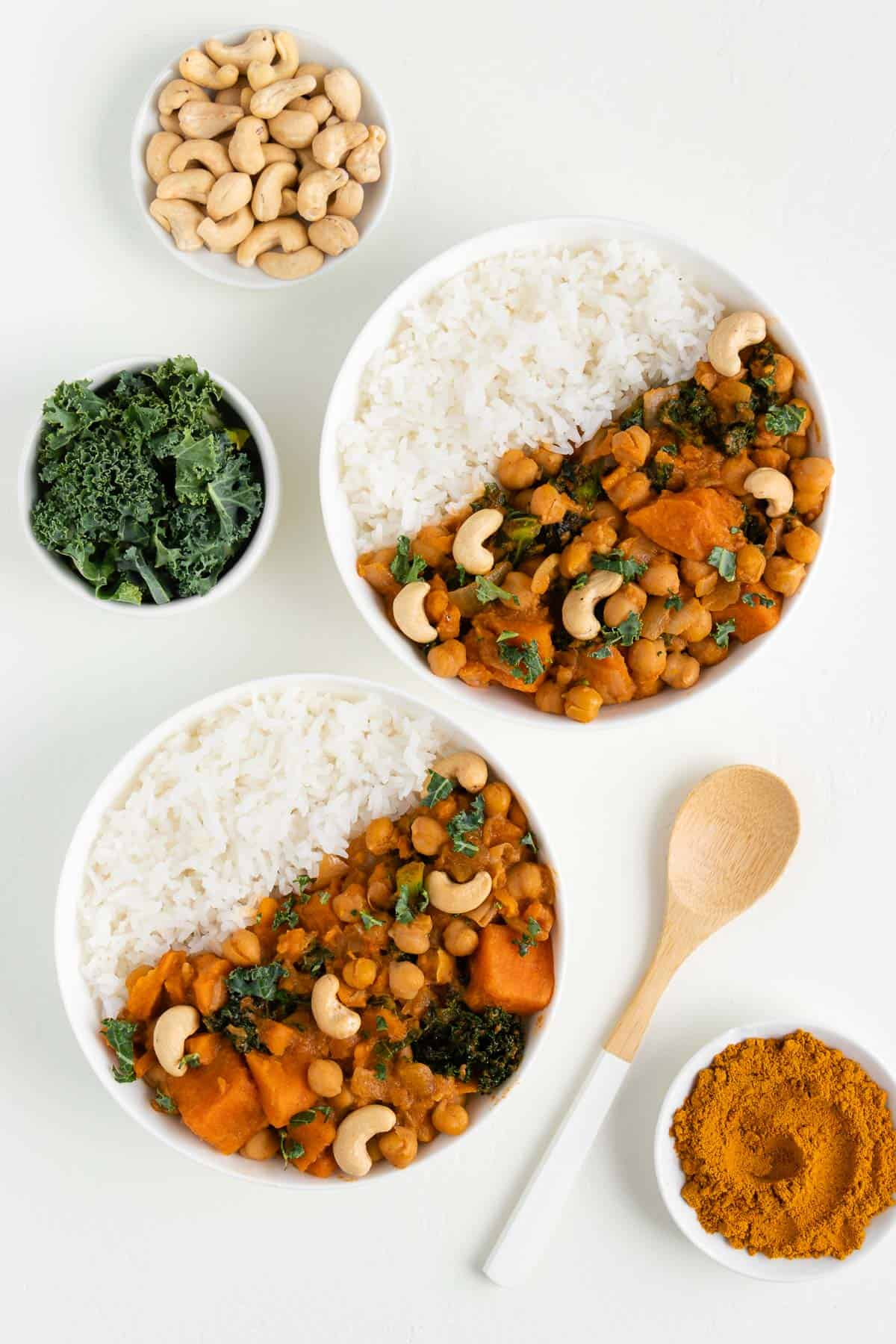 two bowls of sweet potato, kale, and chickpea curry beside a wooden spoon, bowl of kale, and bowl of cashews