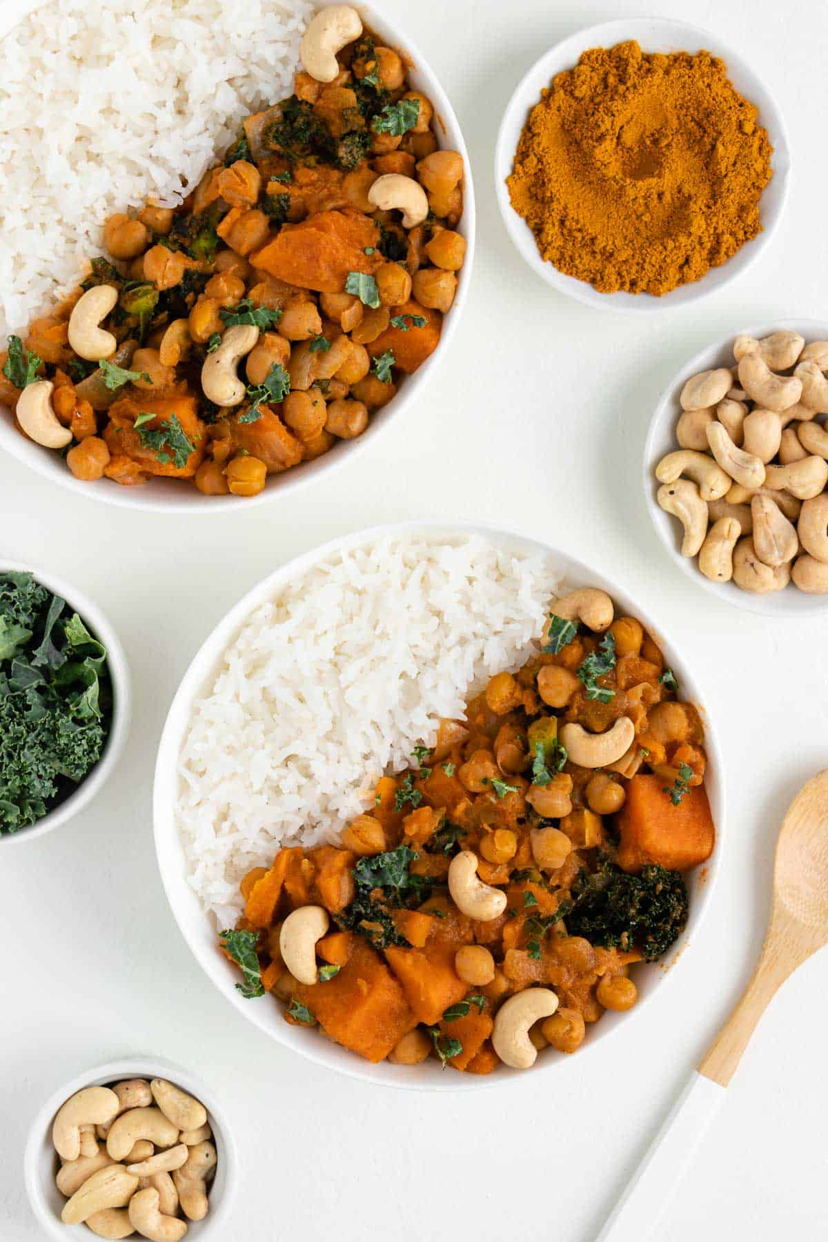 two bowls of white rice and sweet potato curry with chickpeas and kale