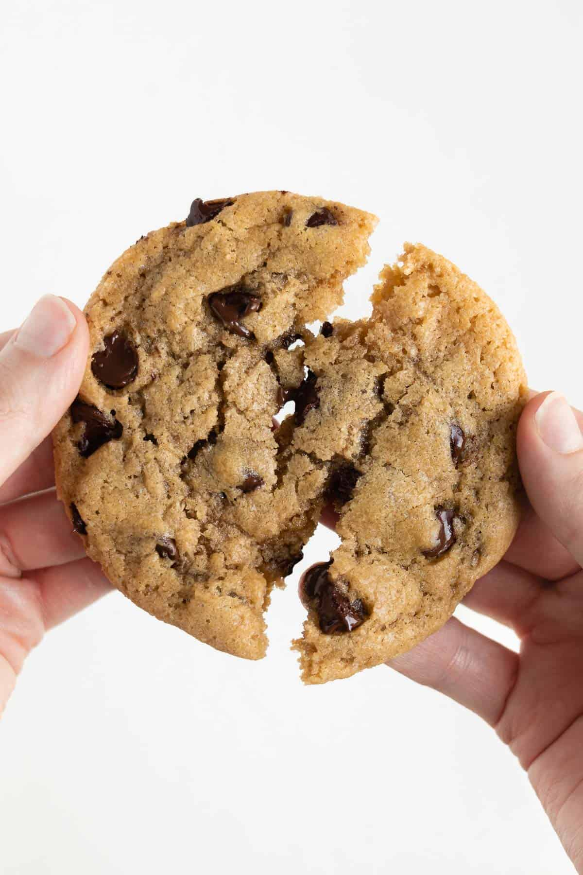 two hands pulling apart a warm and gooey vegan chocolate chip cookie