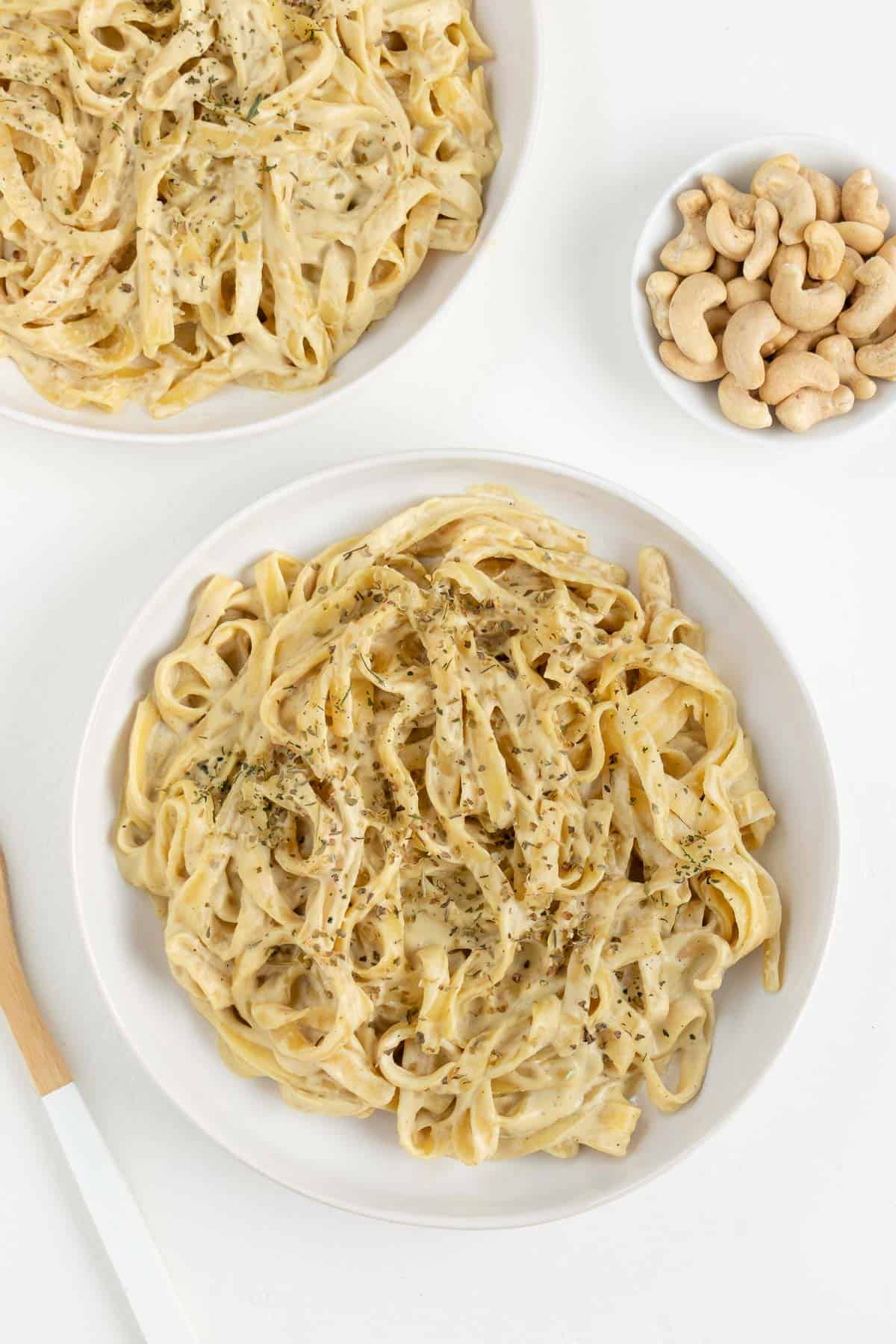 vegan fettuccine alfredo pasta inside two white bowls beside cashews and a wooden fork