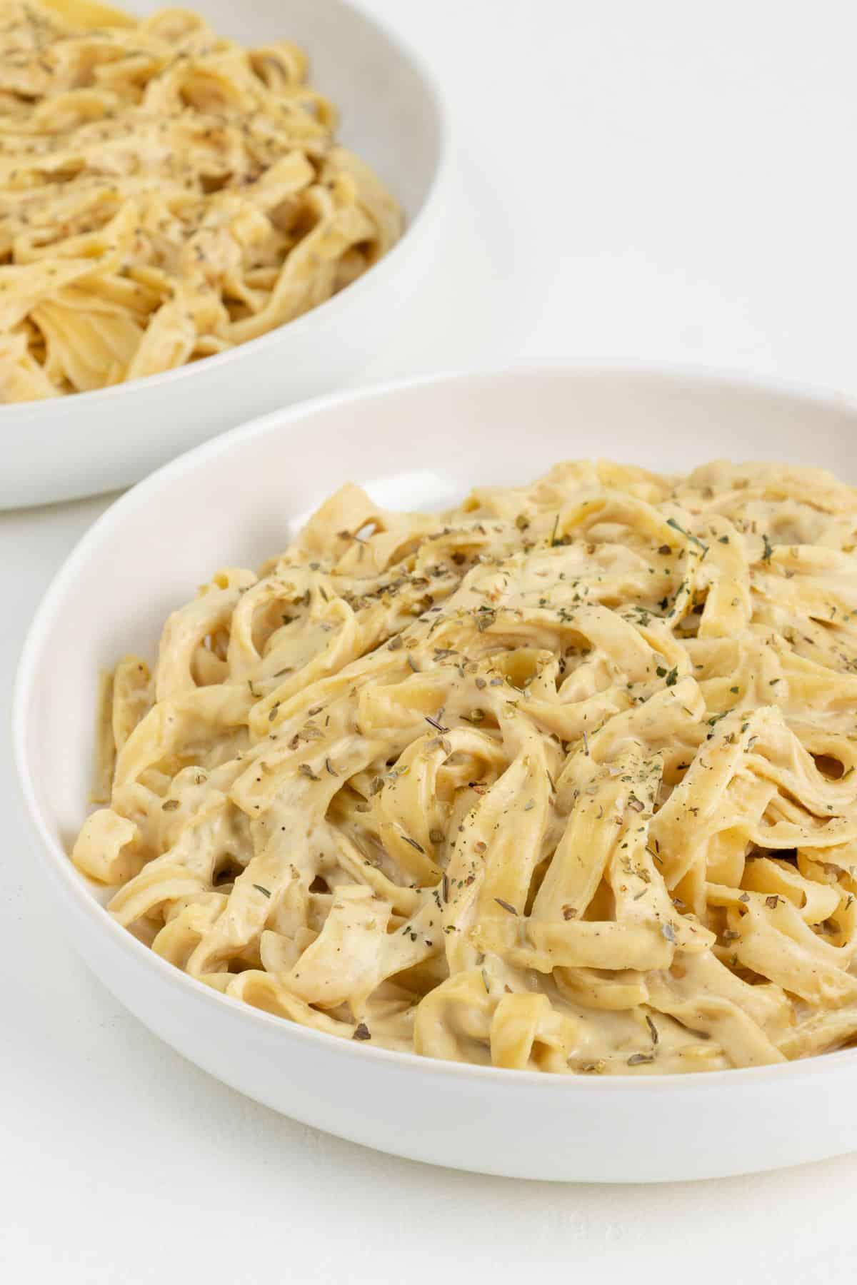 vegan fettuccine alfredo pasta inside two white bowls