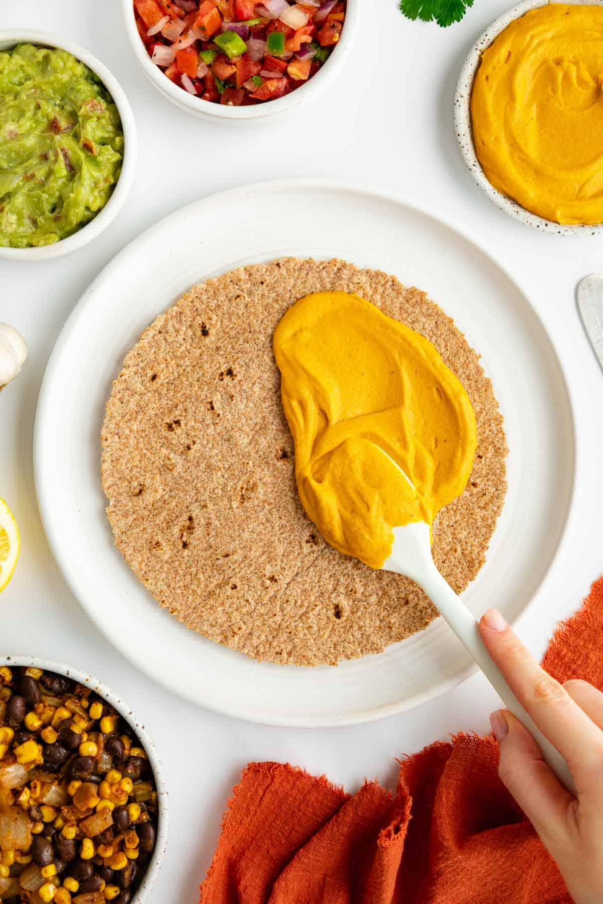 a hand spreading sweet potato cheese on a tortilla, surrounded by bowls of ingredients