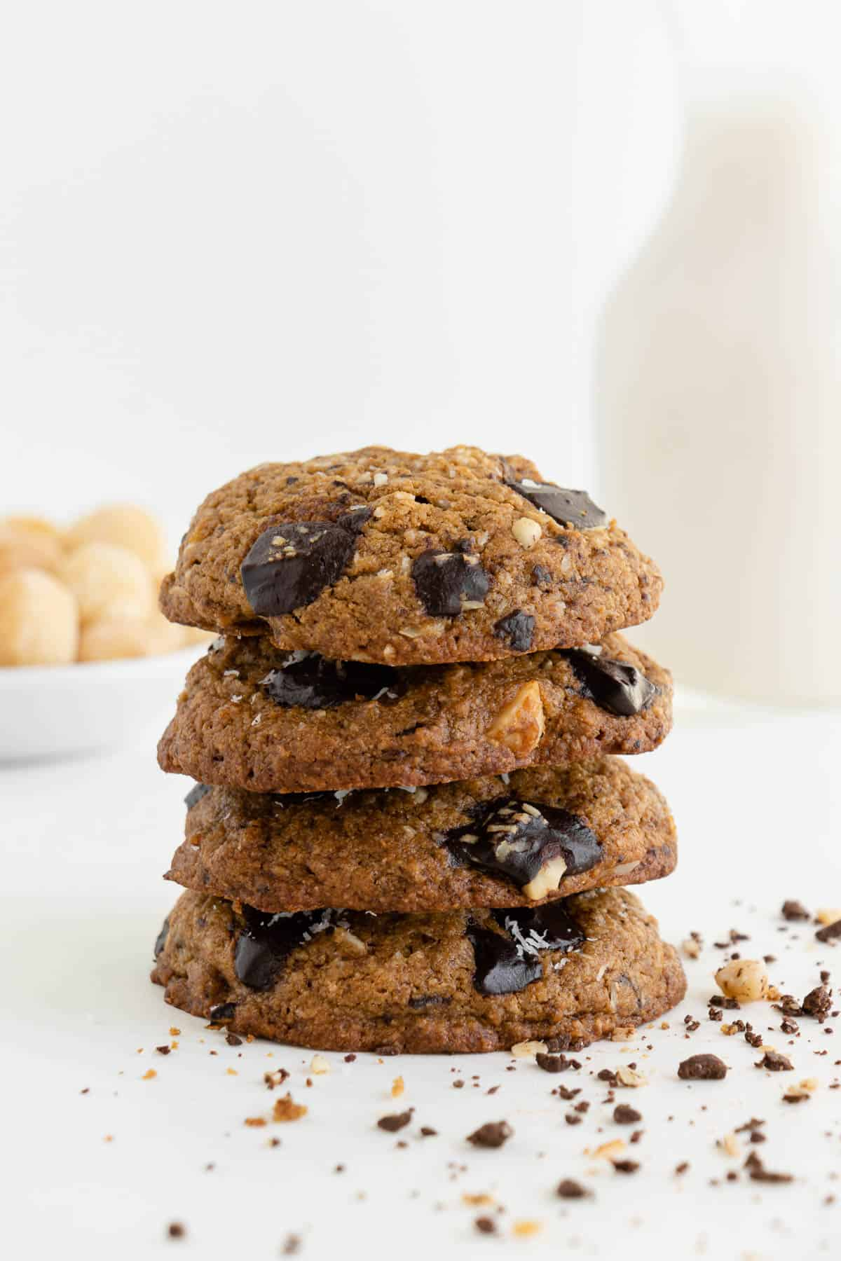 four vegan chocolate chunk hawaiian cookies stacked on top of each other with a glass of almond milk and a bowl of macadamia nuts in the background