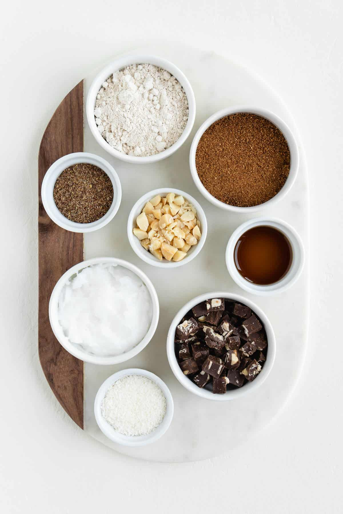 a marble board topped with bowls filled with flour, coconut sugar, shredded coconut, macadamia nuts, chocolate, coconut oil, and ground flaxseed