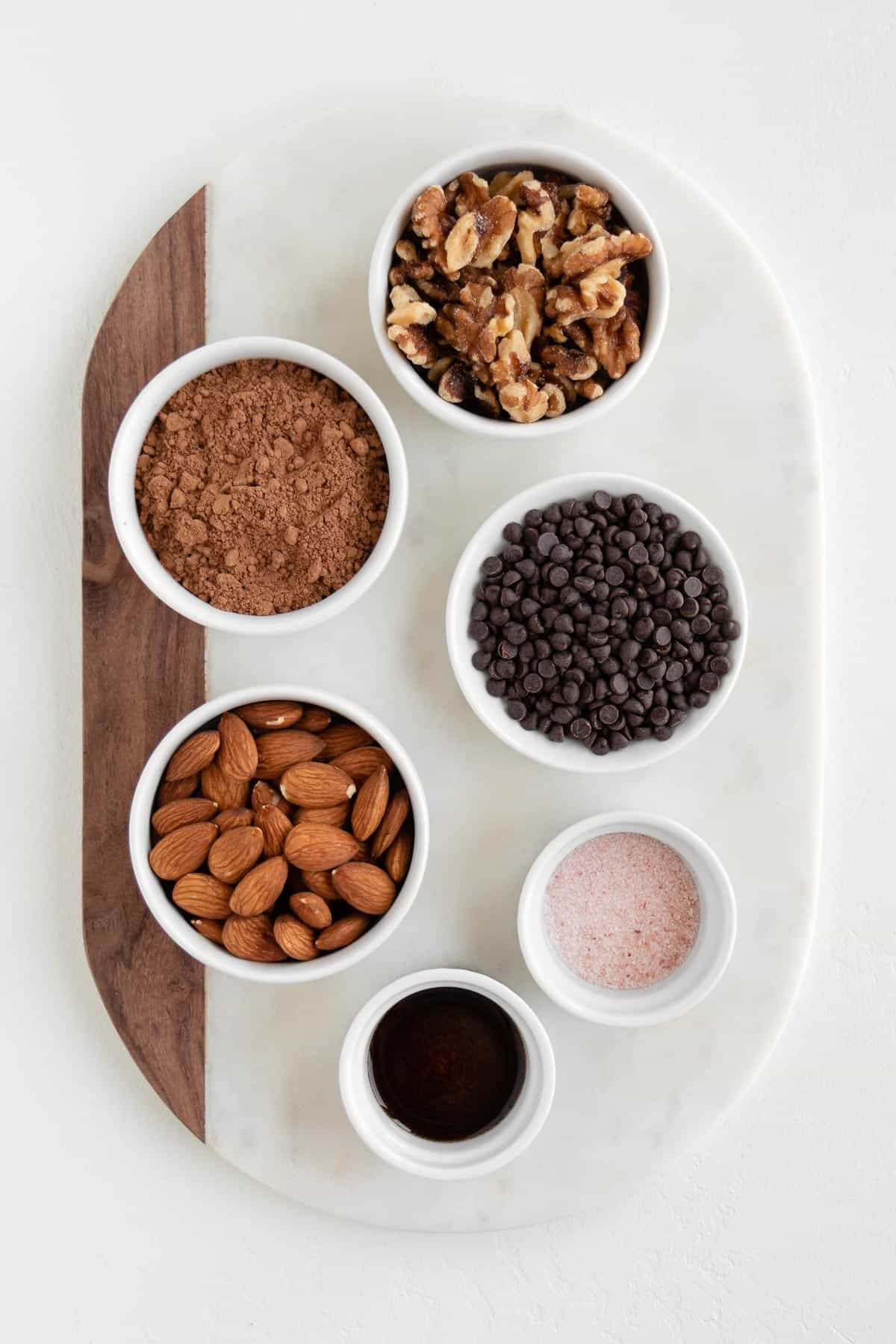 small bowls of walnuts, almonds, cacao powder, chocolate chips, vanilla, and salt on a marble board