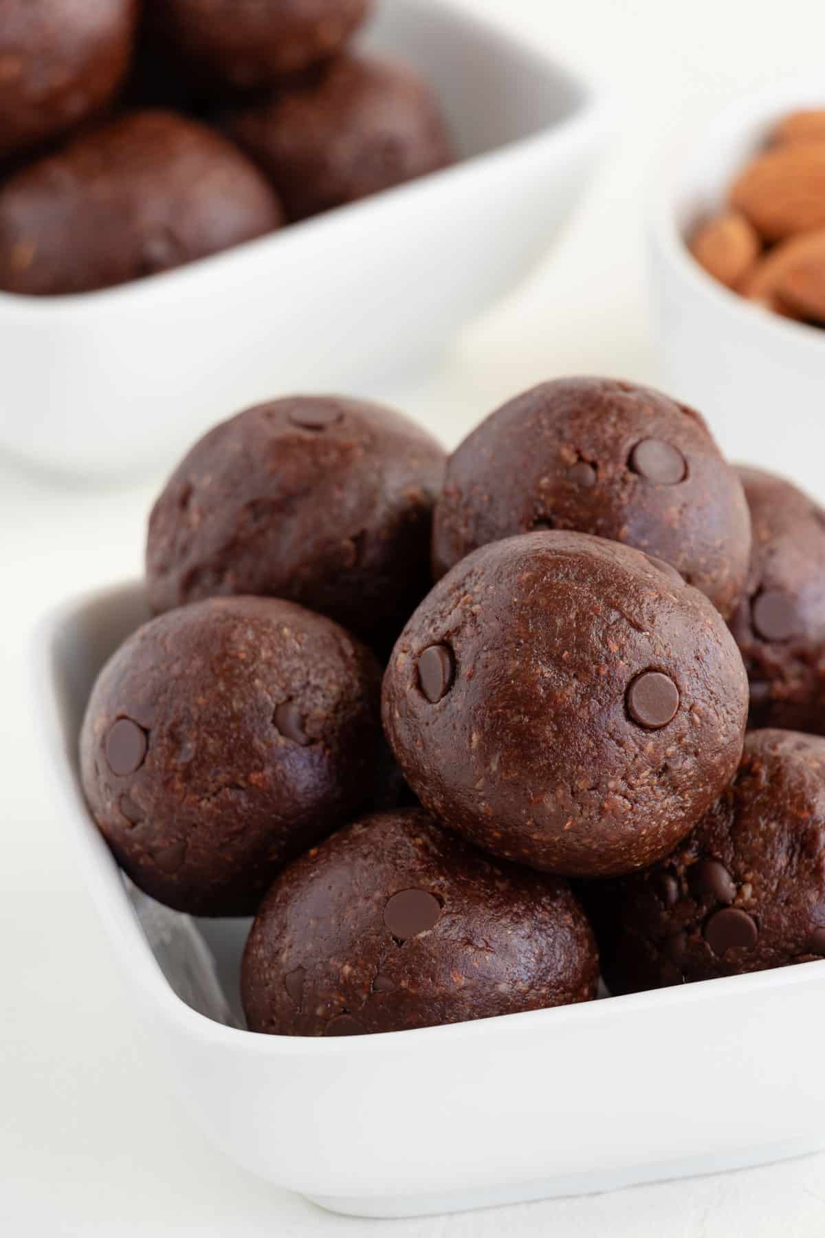 no bake brownie bliss balls stacked inside a square white bowl