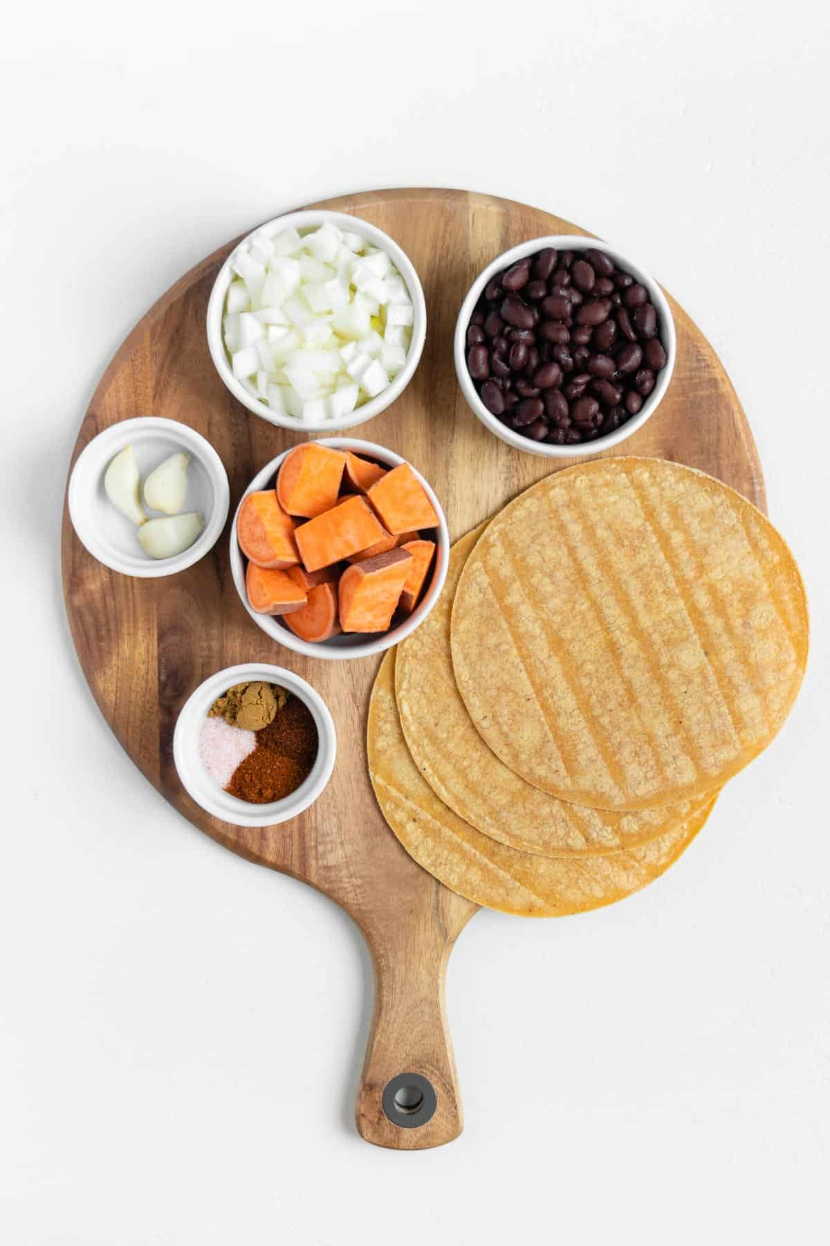 white bowls filled with cubed yams, beans, onion, garlic, spices, and corn tortillas on a round wooden cutting board