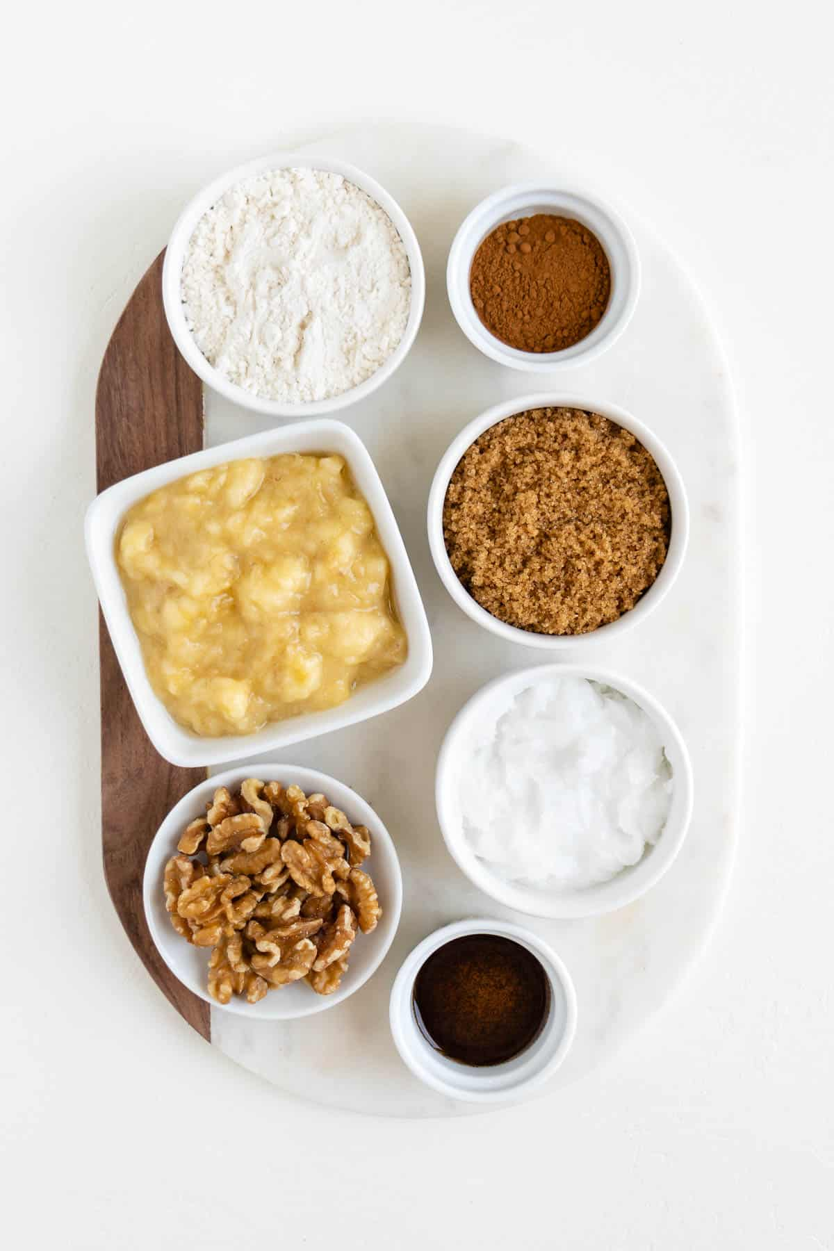 mashed bananas, brown sugar, walnuts, flour, cinnamon, and vanilla extract in white bowls on a marble board
