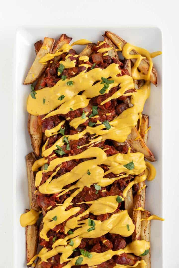 vegan chili cheese fries on a white rectangular plate