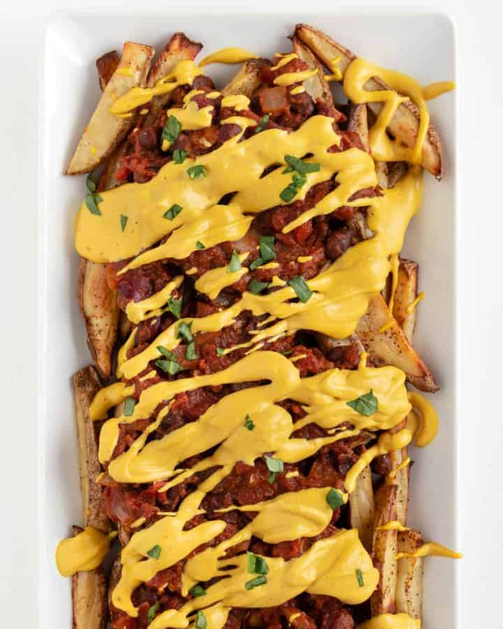vegan chili cheese fries on a white rectangular plate