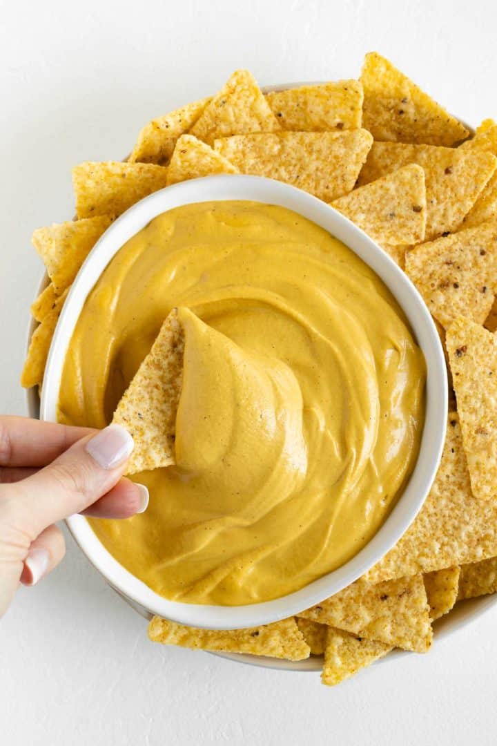 a hand dipping a corn tortilla chip into a bowl of vegan nacho cheese surrounded by more tortilla chips