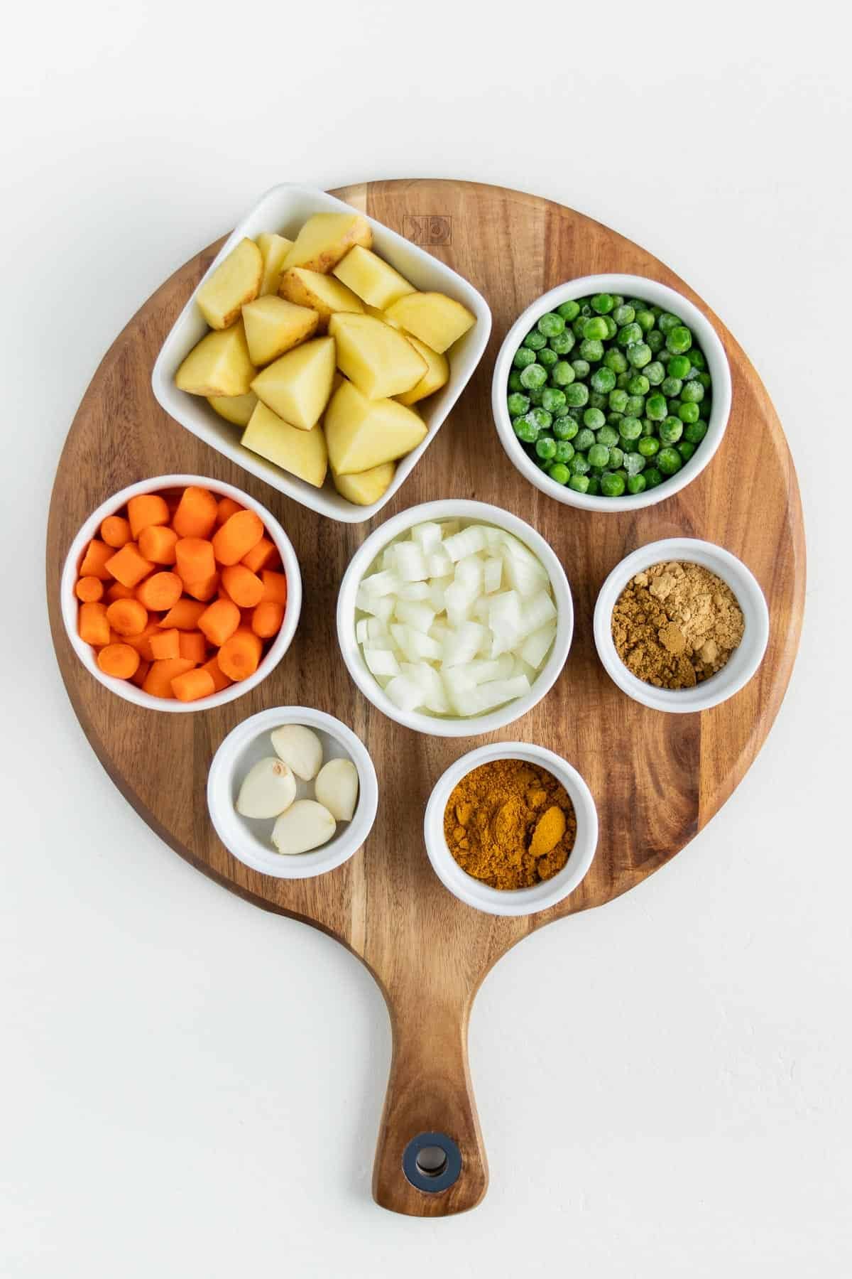 small white bowls filled with potatoes, green peas, carrots, onion, garlic, and spices on a round wooden board