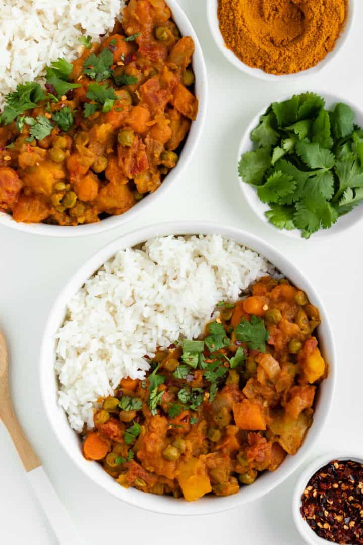 two bowls of vegan potato curry with rice beside a wooden spoon, bowl of red pepper flakes, and bowl of cilantro