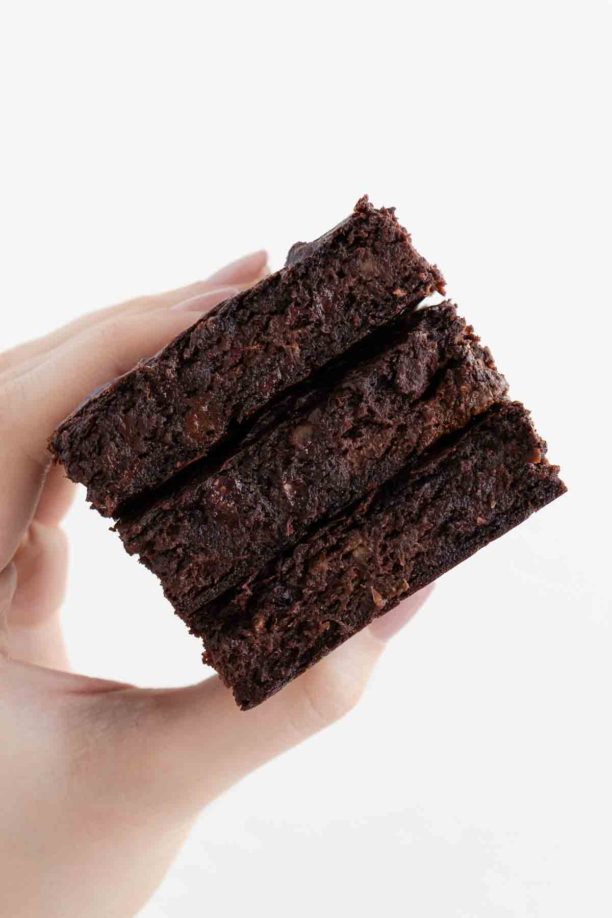 a hand holding a stack of three vegan protein brownies