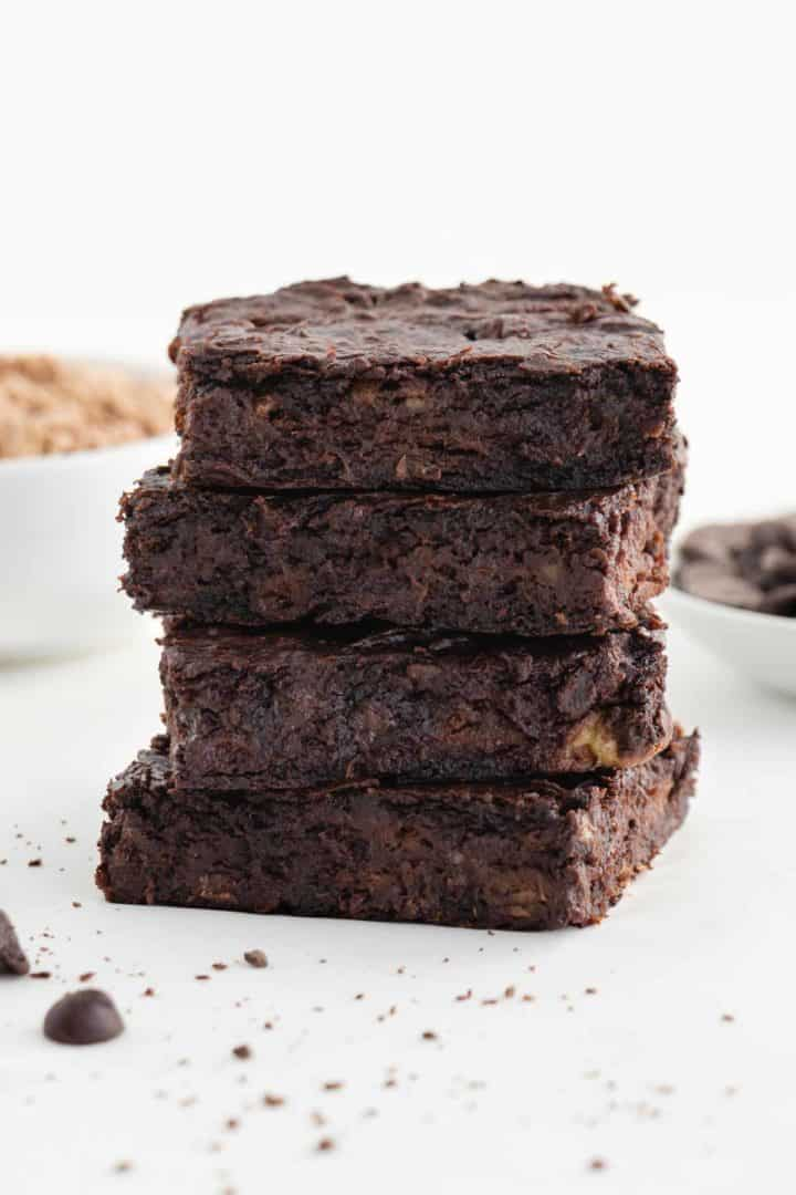 a stack of four flourless vegan protein brownies in front of a bowl of chocolate chips and a bowl of chocolate protein powder