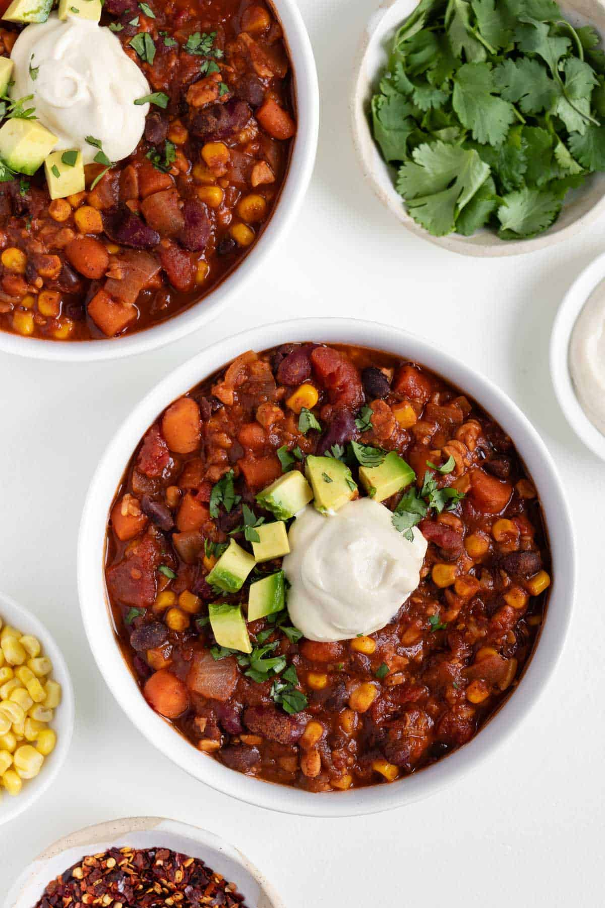 two bowls of vegan tempeh chili surrounded by bowls of cilantro, corn, and cashew sour cream