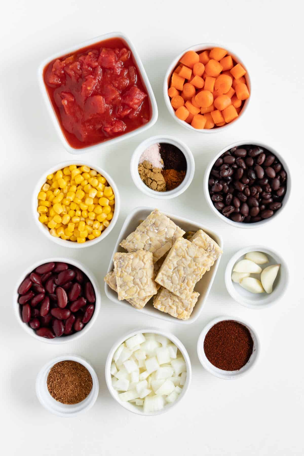 diced tomatoes, carrots, corn, black beans, soy protein, kidney beans, onion, garlic, and spices in small white bowls