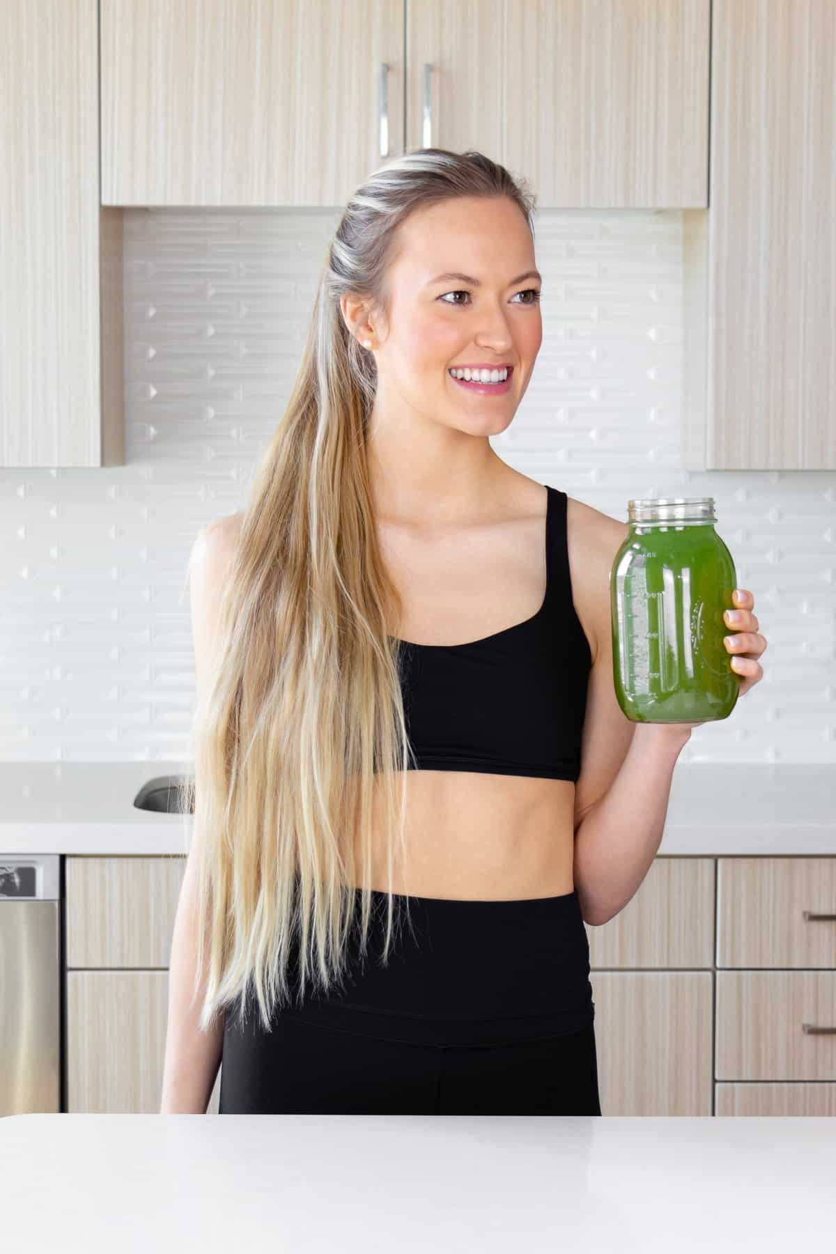 kaylie wearing activewear while holding a mason jar filled with green juice in the kitchen